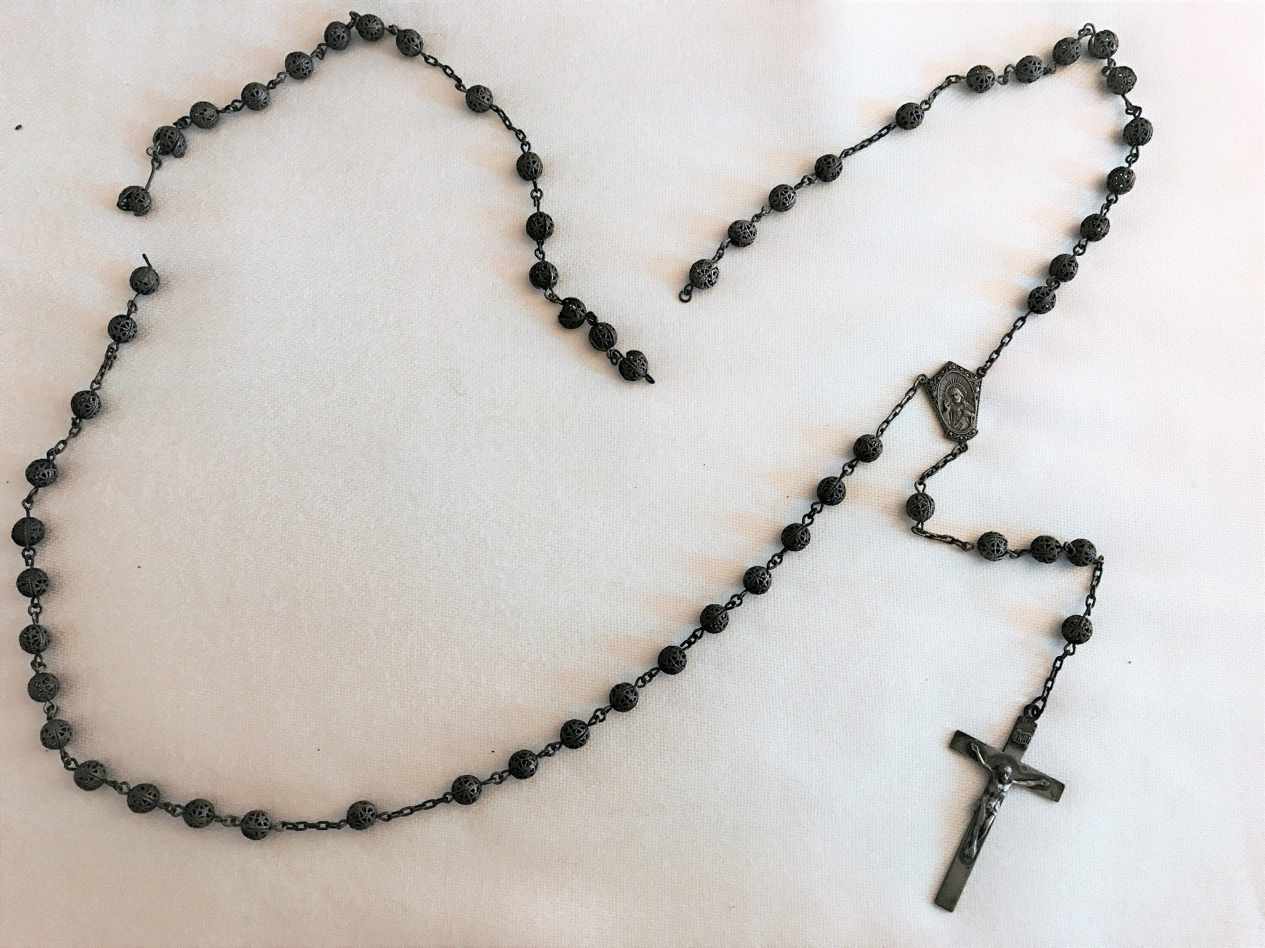 This vintage rosary was made of sterling silver filigree beads with sterling silver crucifix and centerpiece. Two of the beads were badly damaged and the rosary itself was so tarnished that it appeared black.