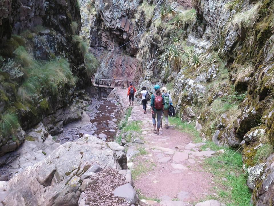 Group trekking through scenic gorge above Huchuy Qosqo ruins.jpg