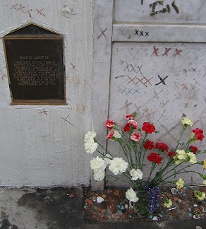 "Marie Laveau's tomb is covered with the letter ""X""— the beads and flowers are offerings by visitors"