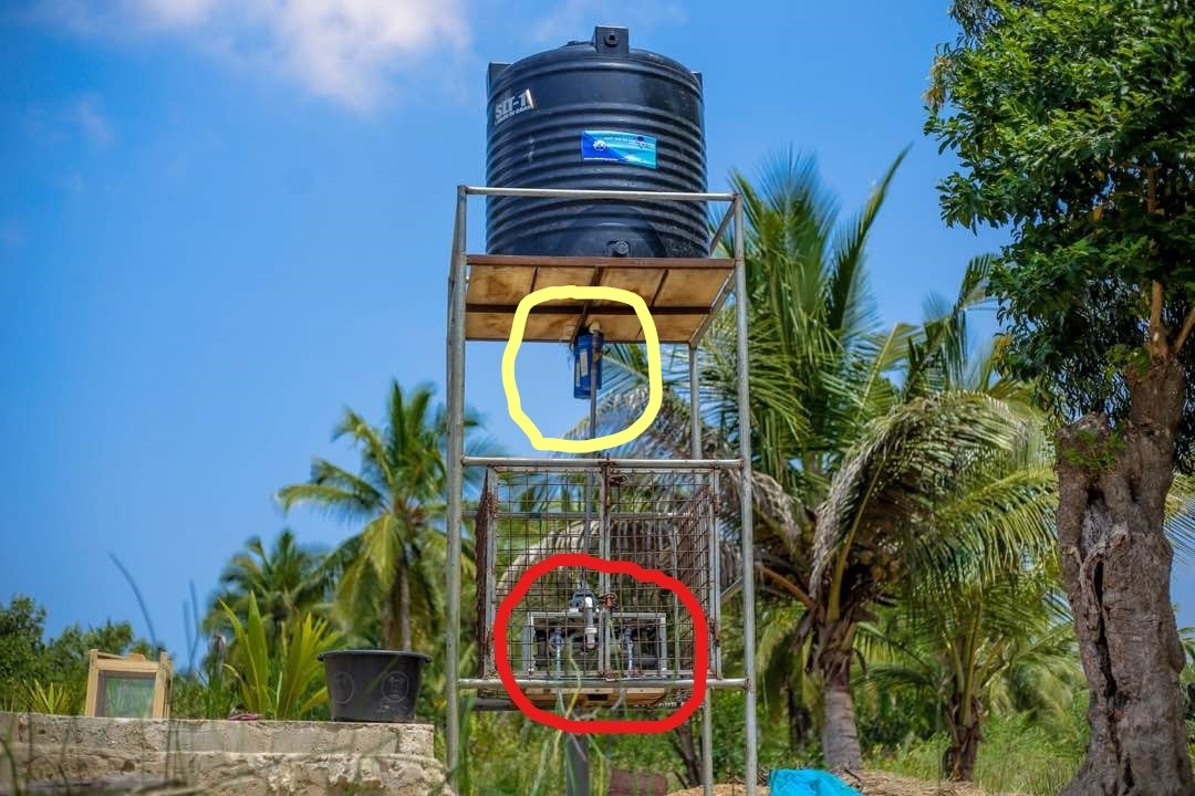 NUF500 device – Dirty water pumped up to black tank by a very small gasoline pump; when the valve of the device (red circle) is opened the dirty water flows out of the black tank through two prefilters to reduce silt (yellow circle), then through the device to produce pure water.