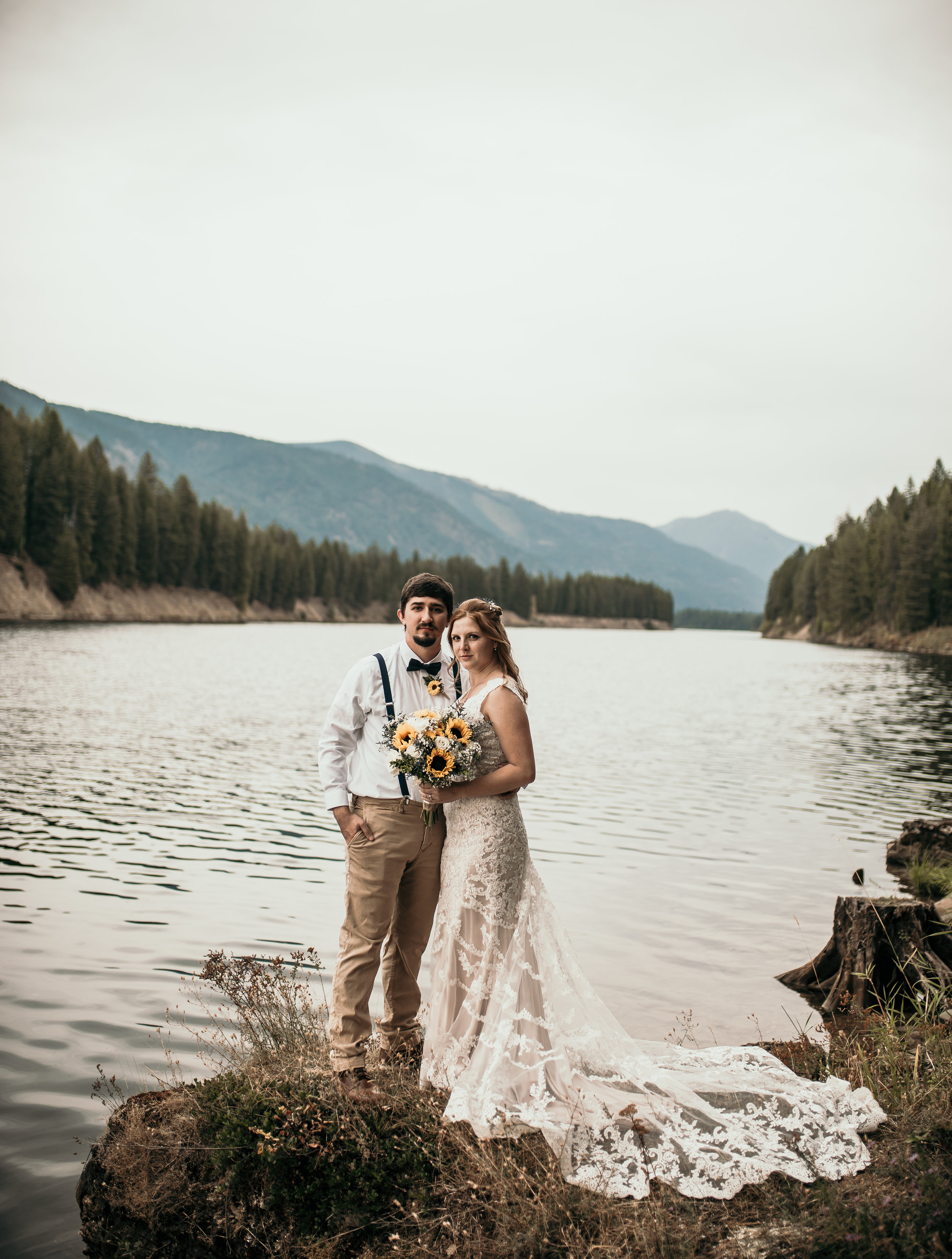 Bride and Groom standing by a river in Herron, Montana smiling at the photographer