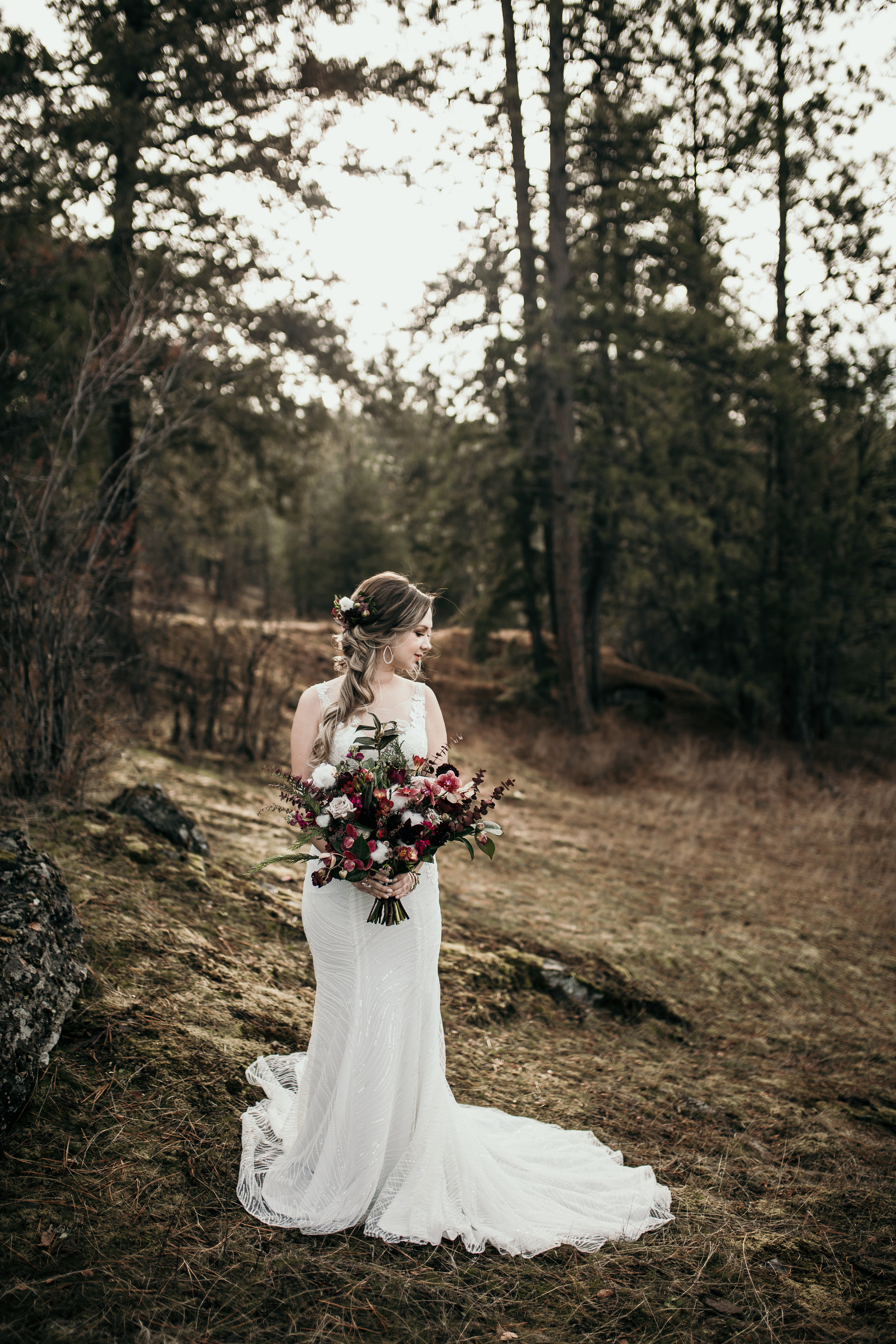 Bride standing in a forest during her wedding on a mountain top.