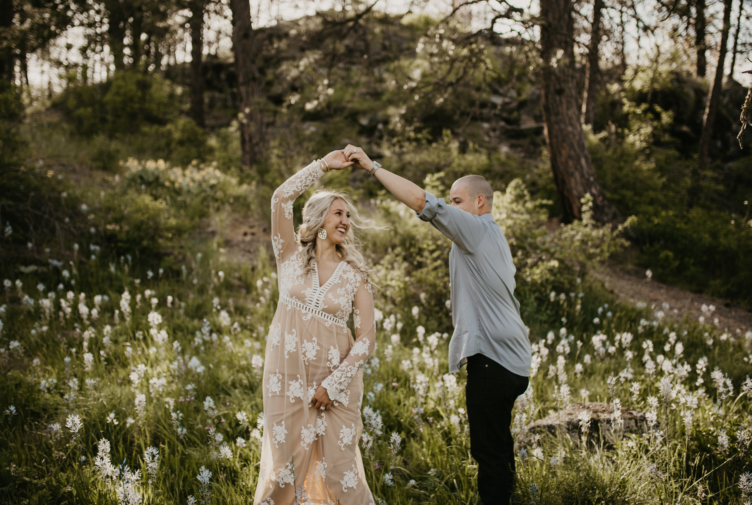 Couple dancing during engagement session in a field of wildflowers