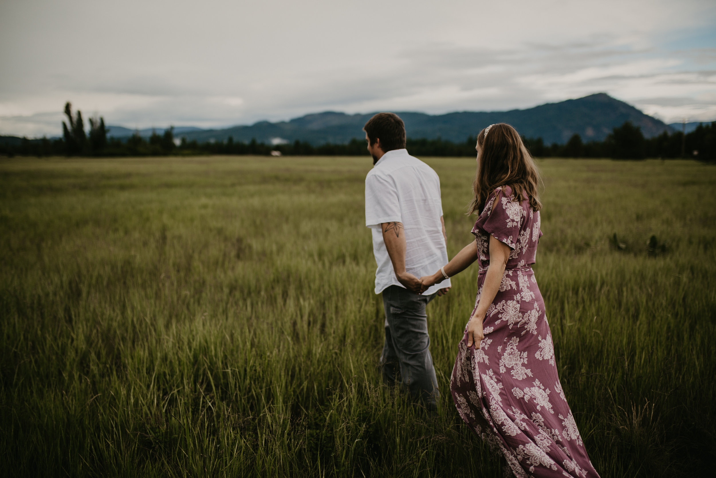Bride and Groom walking in a North Idaho field holding hands
