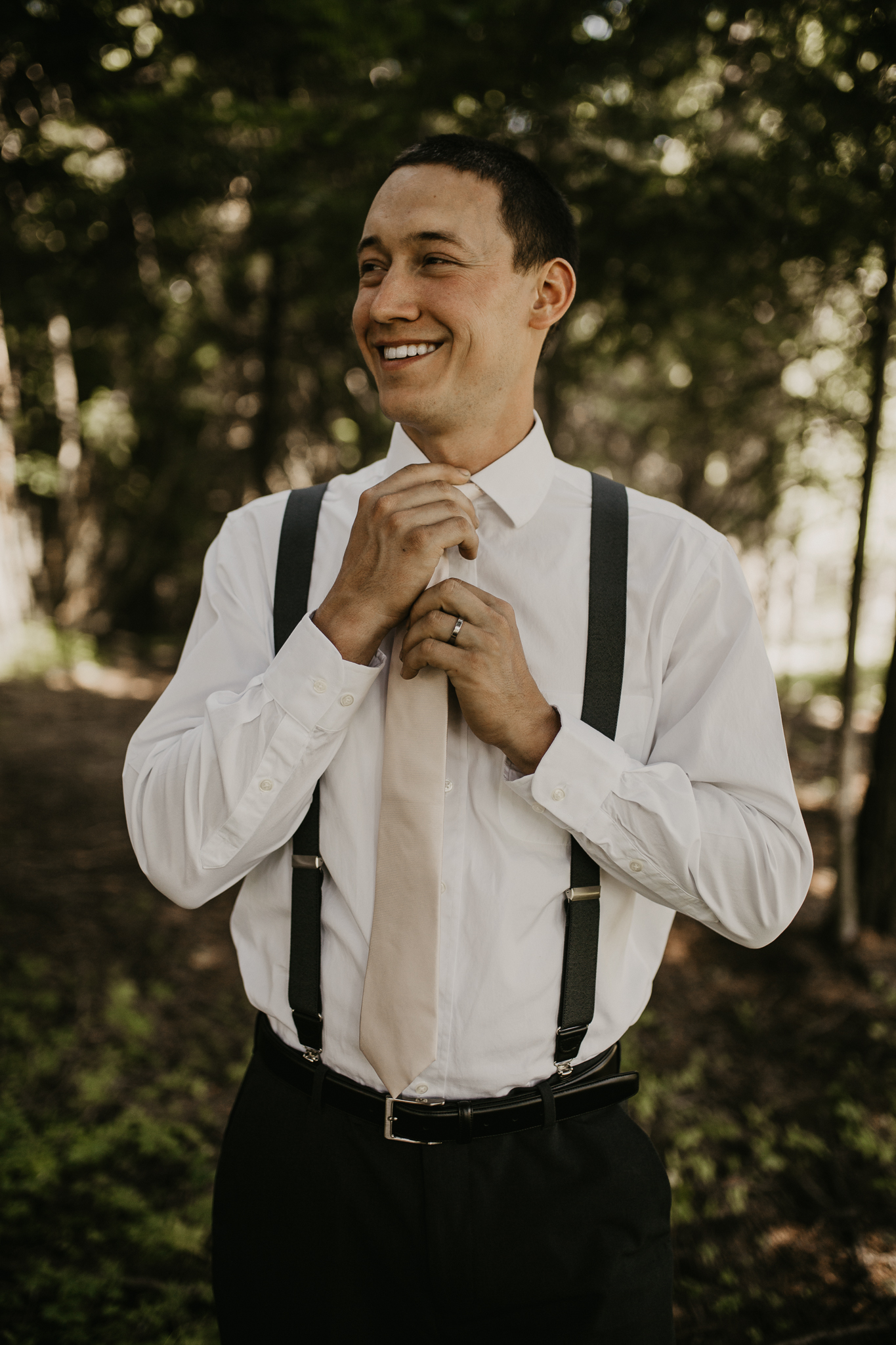 Groom portraits being taken in a forest in the PNW