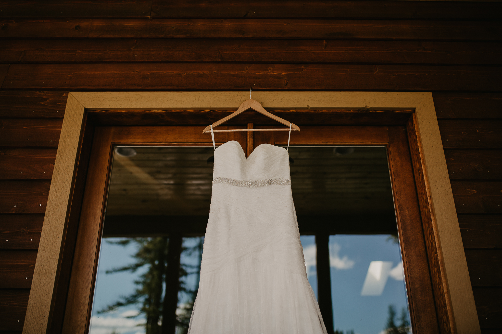 Wedding dress detail shot hung at a rustic log cabin.