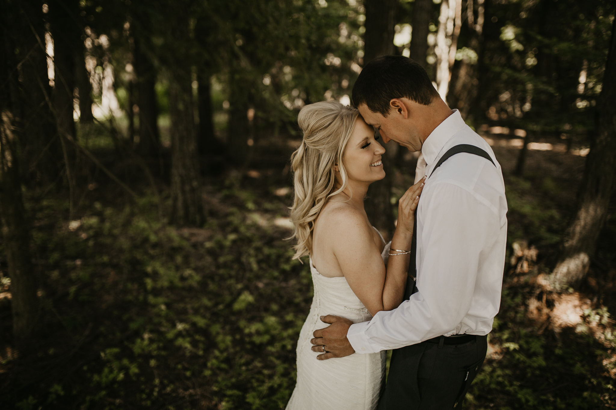 Bride and Groom snuggling in the forest during photoshoot