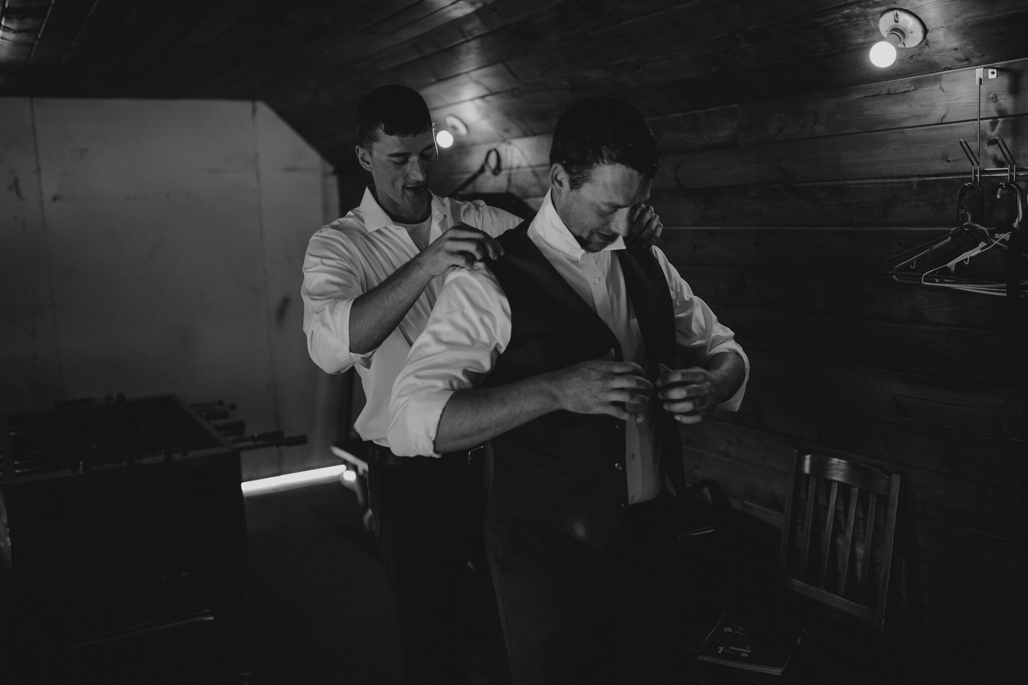 Groomsman helping the groom get ready for his first look