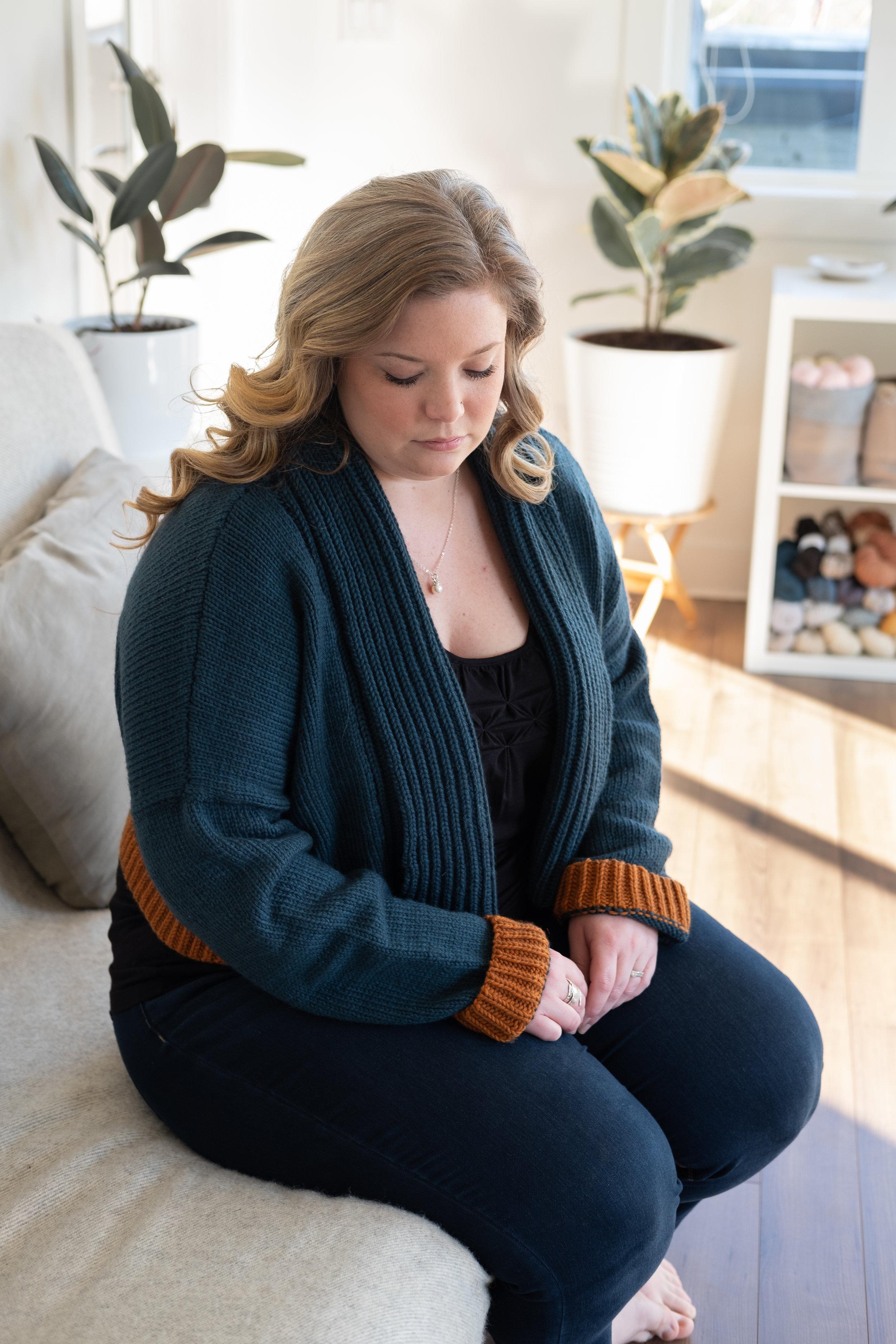 Larissa wearing Gilwell cardigan sits looking down.