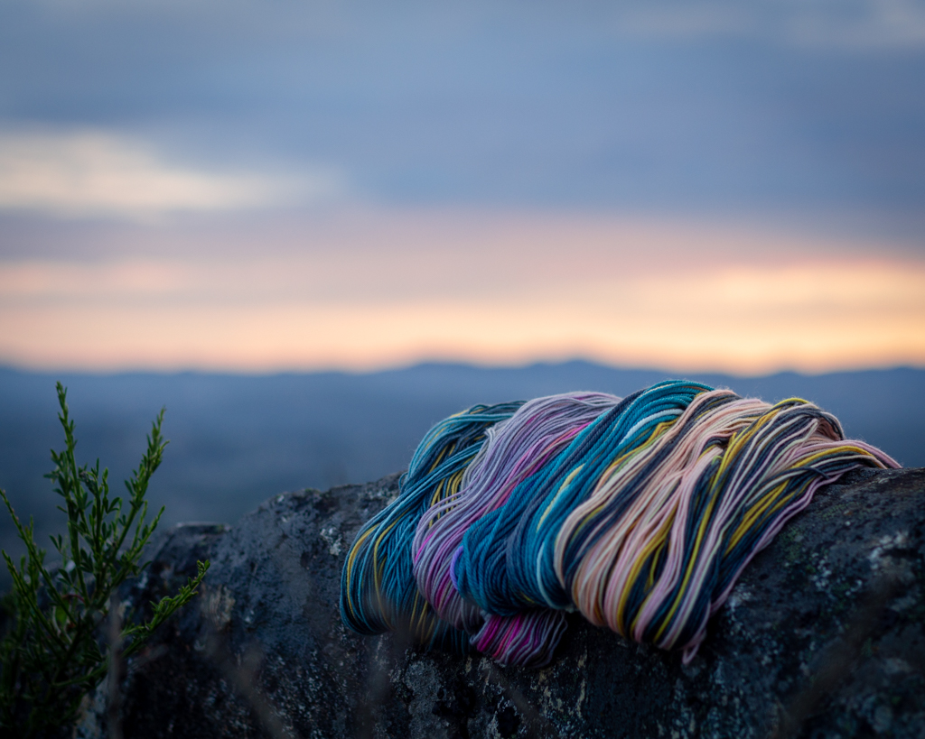 Yarn in shades of pink, grey, gold, blue, and purple are draped over a rock in front of a vibrant sunset. The sky reflects the colours of the yarn.