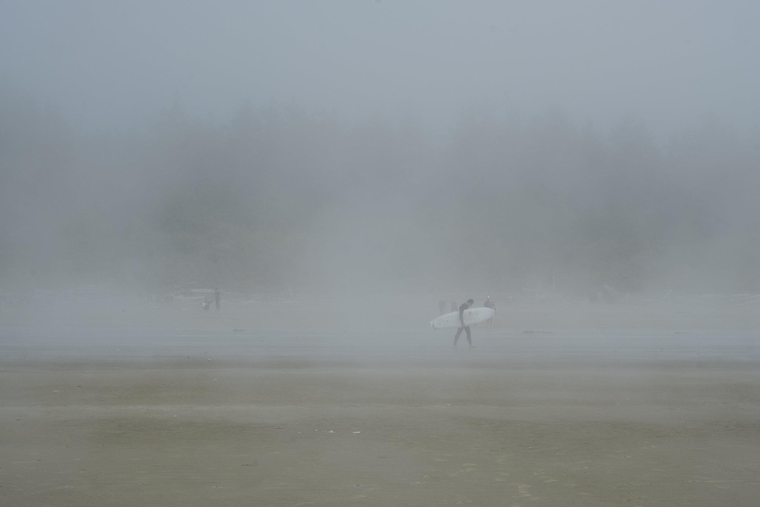 A surfer walking through a misty morning, Long Beach, Tofino