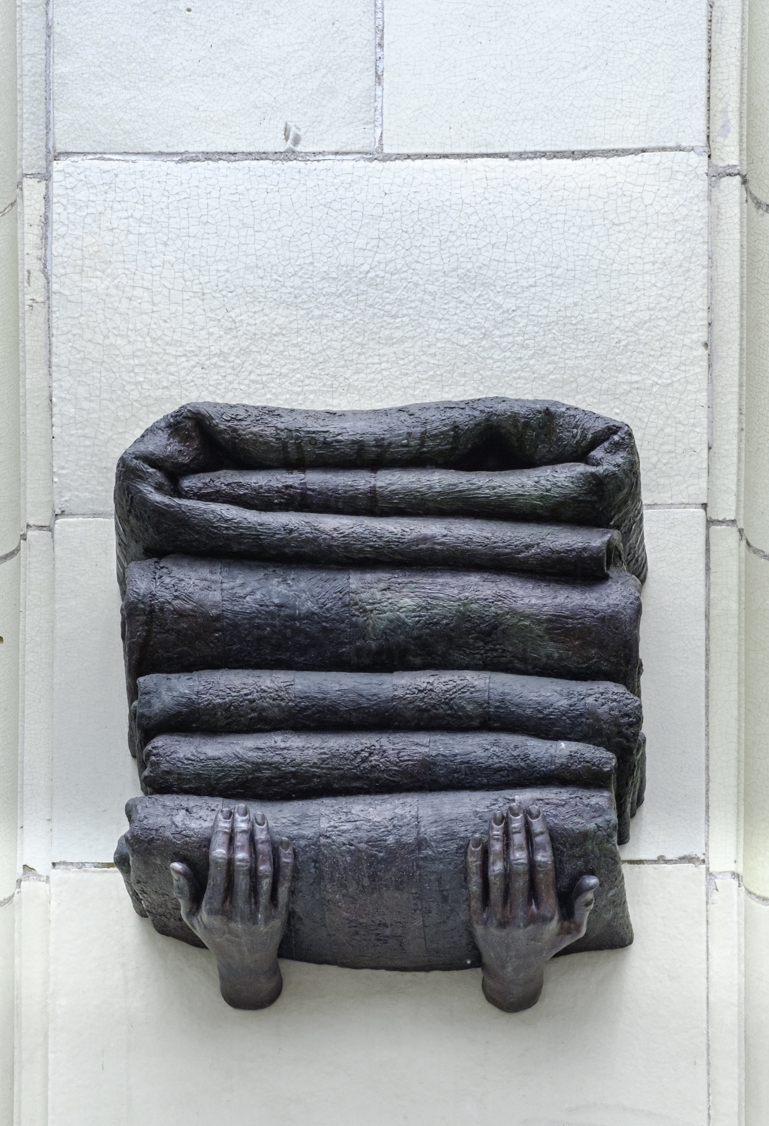A bronze sculpture of hands holding a tall stack of folded blankets. This piece is by artist Crystal Przybille and is part of the  Hands of Time  series.