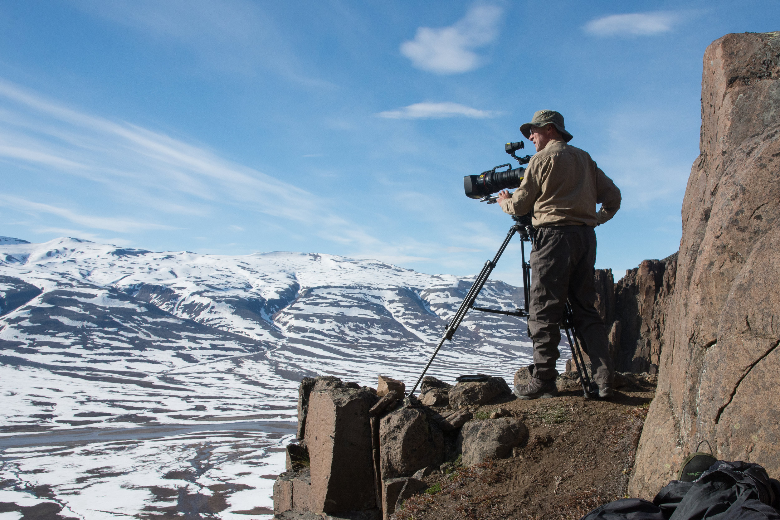 Greenland - Cameraman Barrie Britton prepares to film barnacle geese. The 400 foot basalt cliffs provided unstable filming platforms. Over thousands of years the freeze/thaw cycle has split the rocks. Many of them are balanced delicately on top of each other so the crew had to be extremely careful whenever they were working on, or under, the cliffs. On several occasions the crew witnessed avalanches. (National Geographic/Miguel Willis)