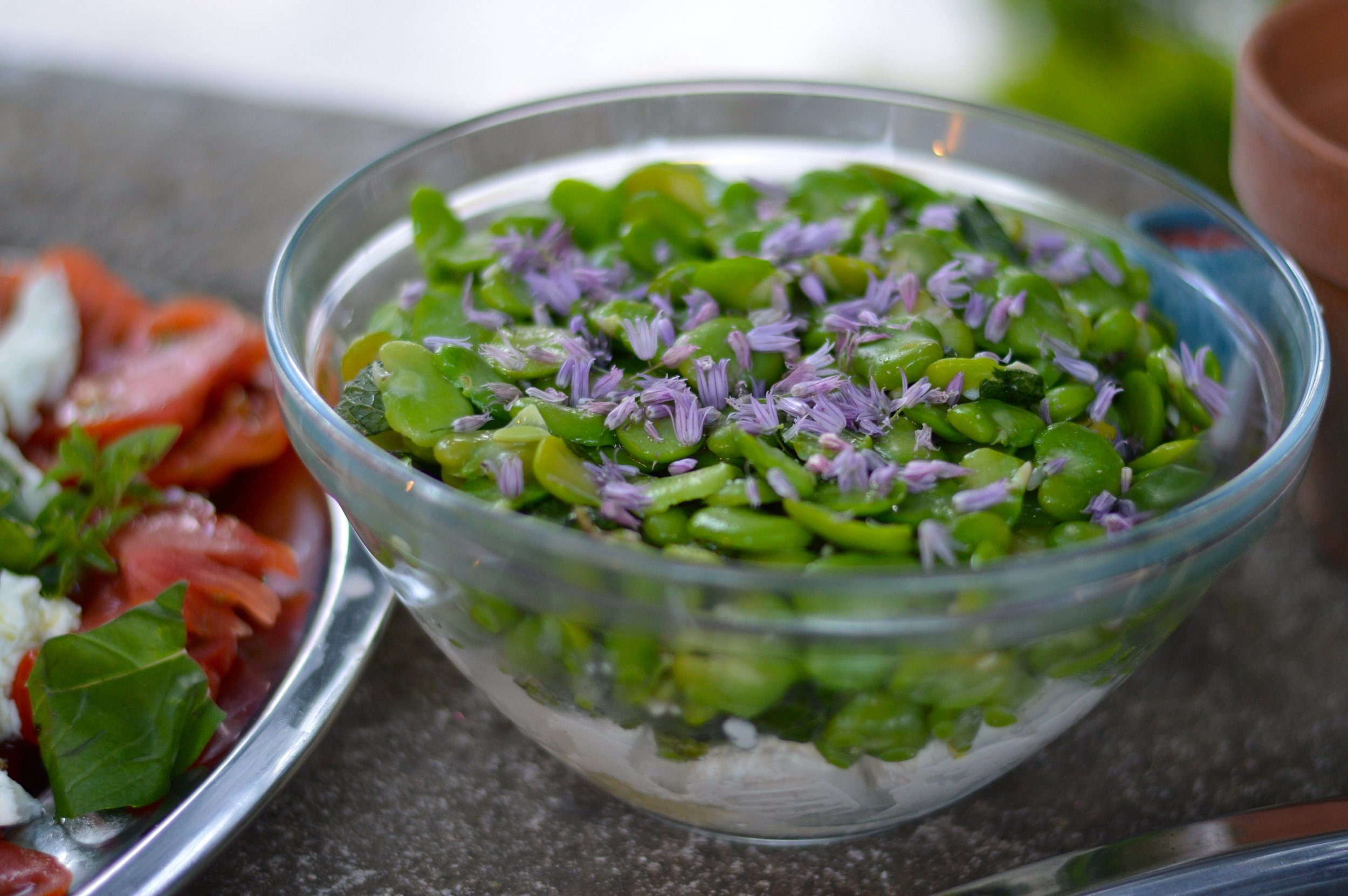 Bowl of bright green beans garnished with flowers