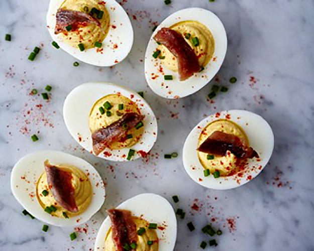 Deviled Eggs with Anchovies and Rosemary served on a marble slab