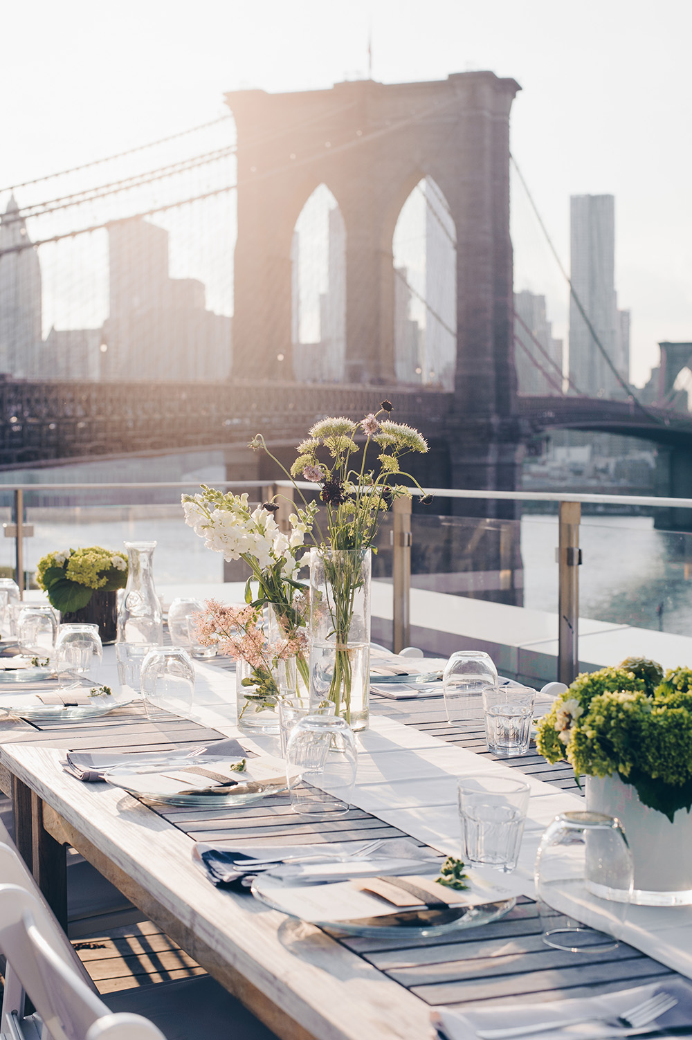 Beautifully set rooftop dinner table at sunset with the Brooklyn Bridge in the background