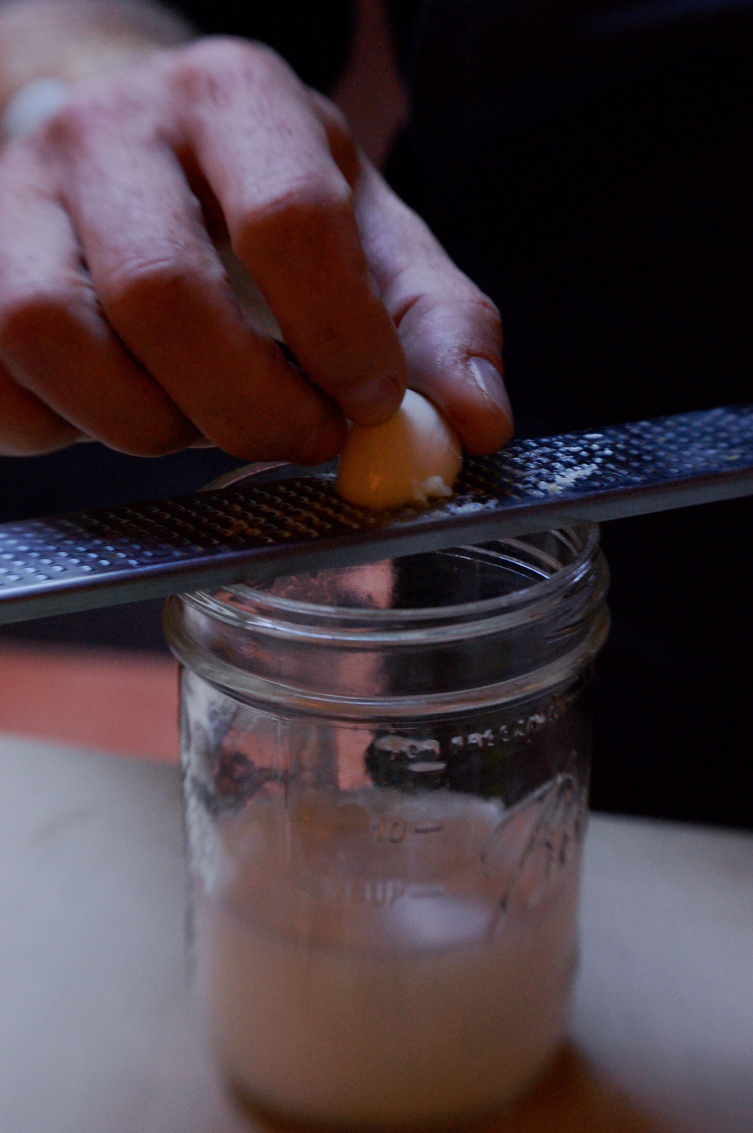 Using a microplane over a mason jar for garlic in a vinaigrette