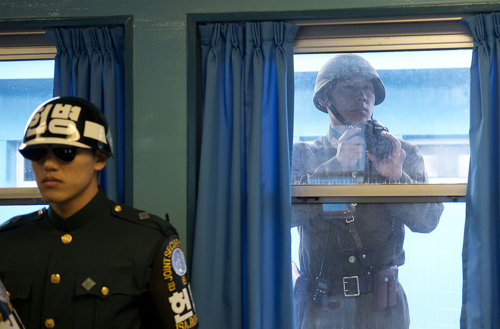 A soldier from the South stand guard as a soldier from the North peers inside
