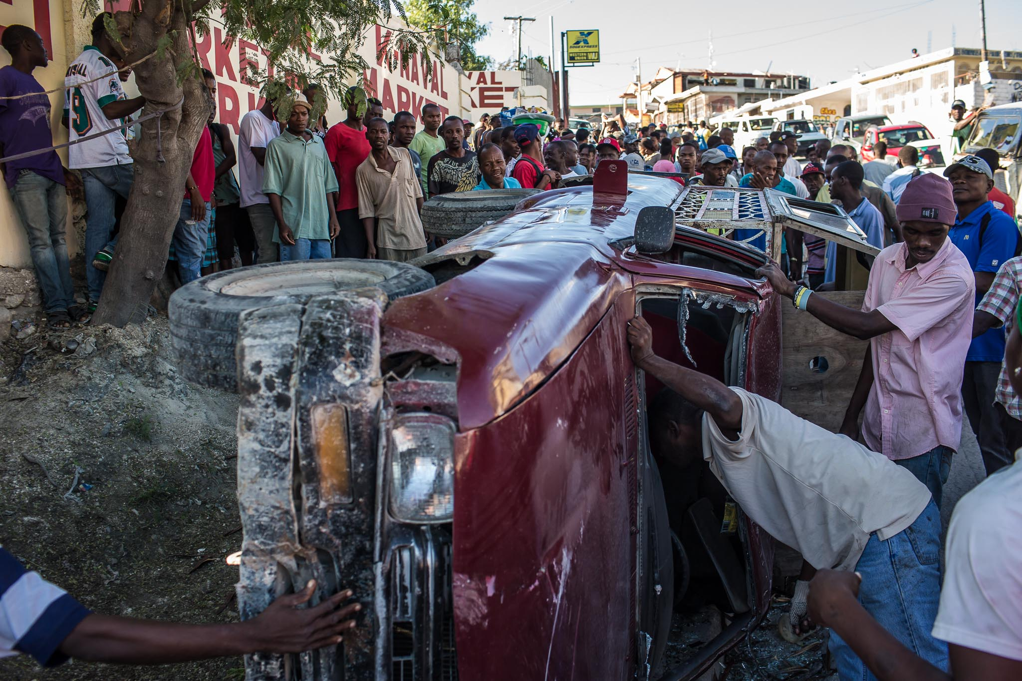 A tap-tap which flipped over during a morning rush-hour accident is inspected by a curious crowd on Thursday, December 18, 2014 in Port-au-Prince, Haiti. No one was injured in the accident.
