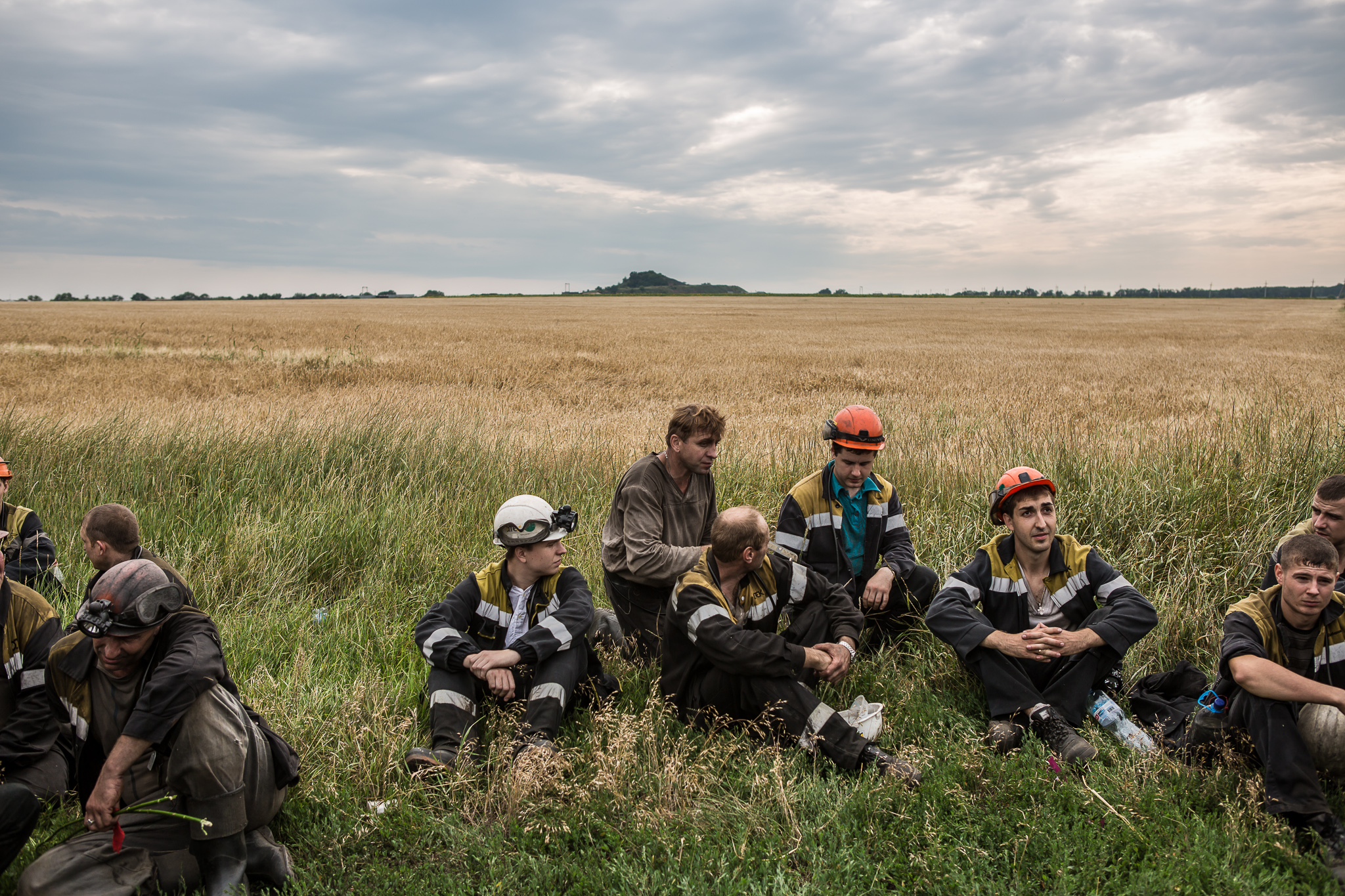 A group of coal miners takes a break after searching fields looking for remnants of Malaysia Airlines flight MH 17 on July 19, 2014 in Grabovo, Ukraine. Malaysia Airlines flight MH17 was travelling from Amsterdam to Kuala Lumpur when it crashed killing all 298 on board including 80 children. The aircraft was allegedly shot down by a missile and investigations continue over the perpetrators of the attack.