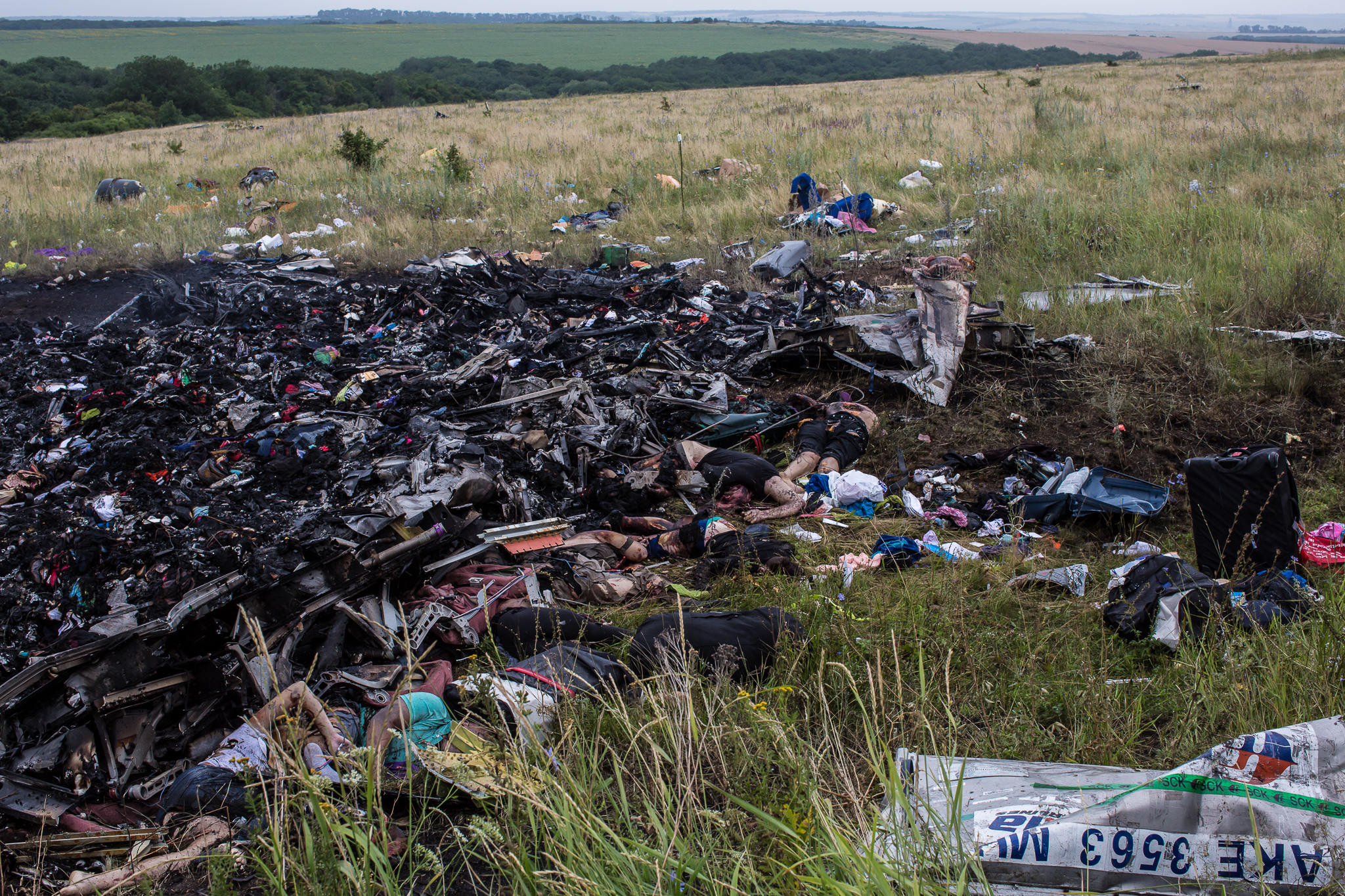 The bodies of victims of the crash of Malaysia Airlines flight MH17 lie among burned wreckage in a field on July 18, 2014 in Grabovo, Ukraine. Air Malaysia flight MH17 travelling from Amsterdam to Kuala Lumpur has crashed on the Ukraine/Russia border near the town of Shaktersk. The Boeing 777 was carrying 298 people.