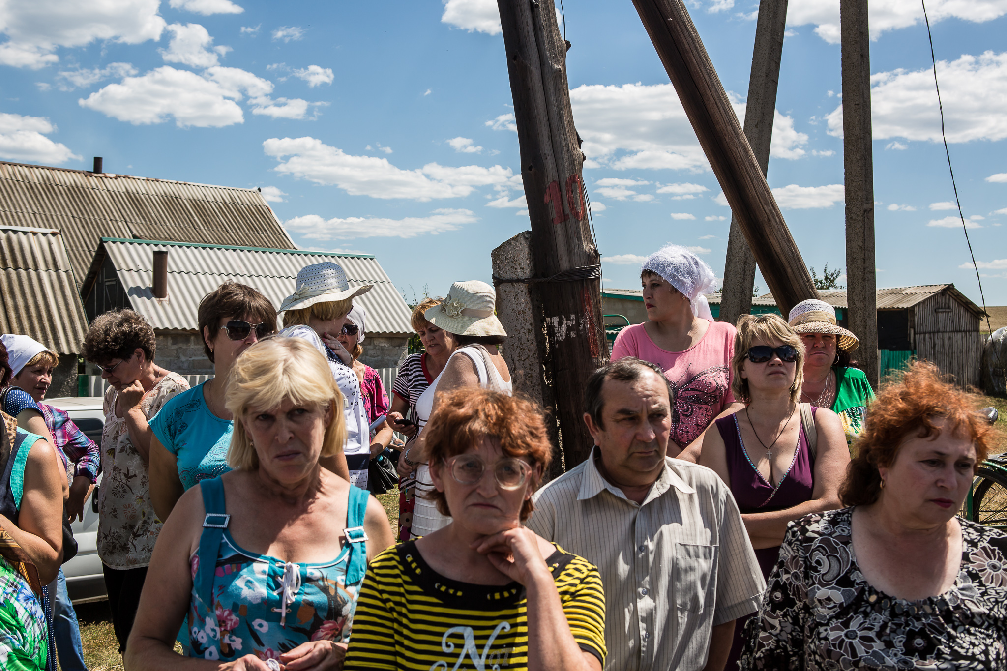 Local residents gather to watch as the bodies of victims of Malaysia Airlines flight MH17 are removed from the scene of the crash on July 21, 2014 in Grabovo, Ukraine. The flight was traveling from Amsterdam to Kuala Lumpur when it crashed killing all 298 on board including 80 children. The aircraft was allegedly shot down by a missile and investigations continue over the perpetrators of the attack.