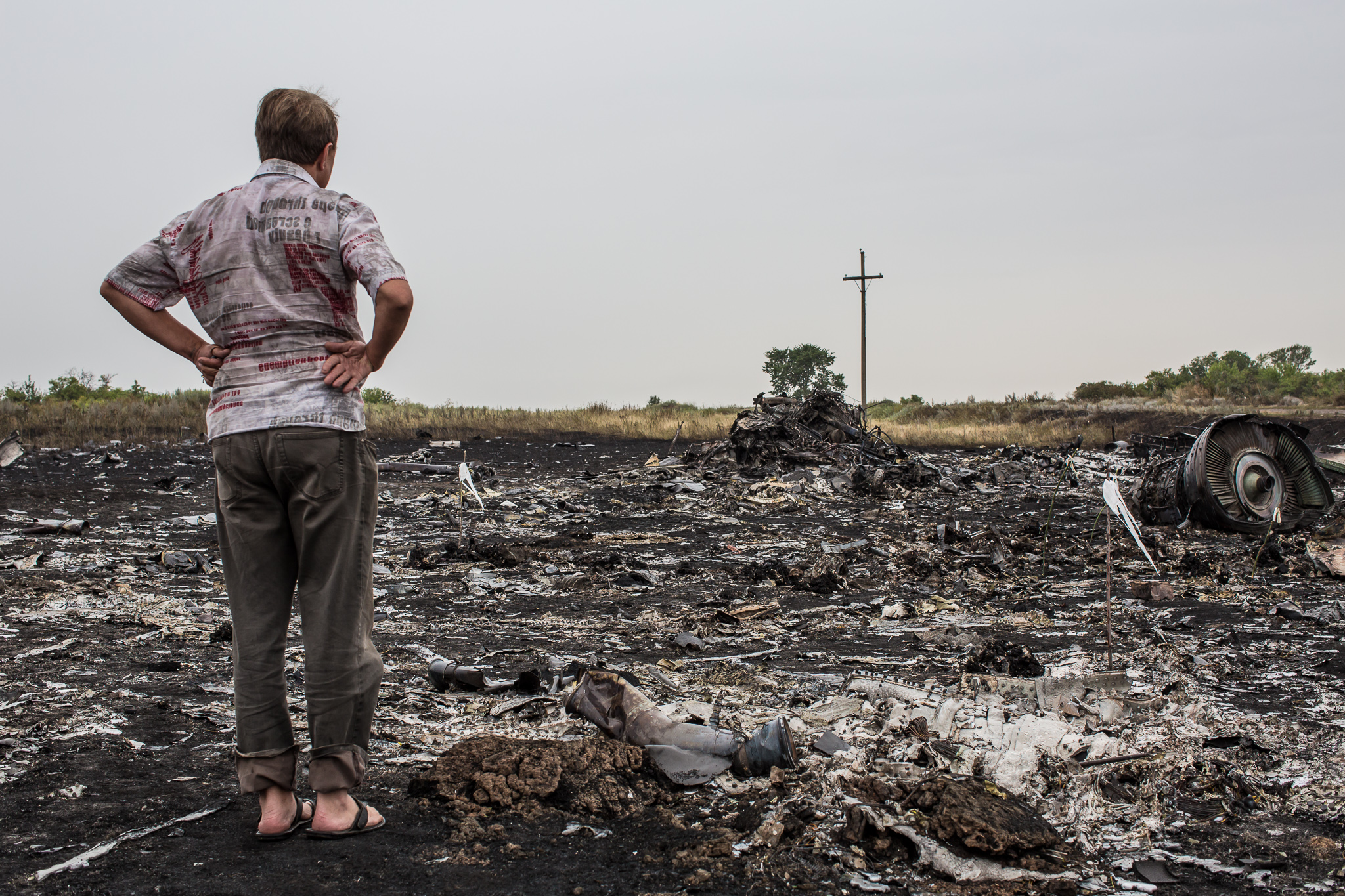 A man looks at debris from the crash of Malaysia Airlines flight MH17 on July 18, 2014 in Grabovo, Ukraine. Malaysia Airlines flight MH17 travelling from Amsterdam to Kuala Lumpur has crashed on the Ukraine/Russia border near the town of Shaktersk. The Boeing 777 was carrying 298 people.