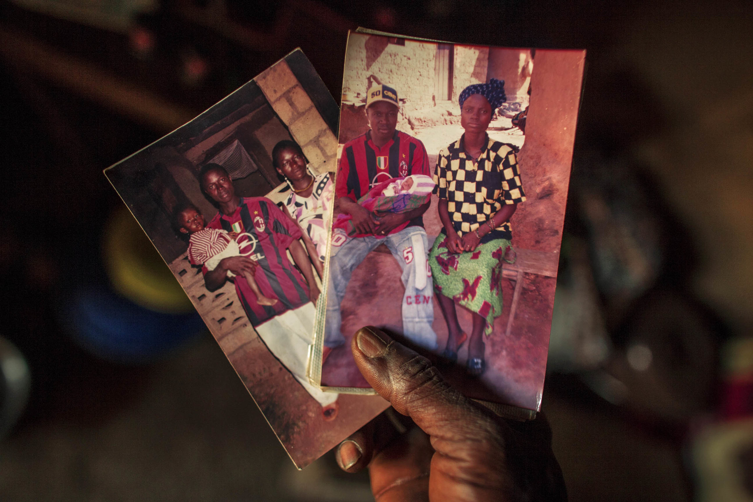 Etienne shows the few photographs he has of his late wife and son. (Photo by Pete Muller/Prime for National Geographic)