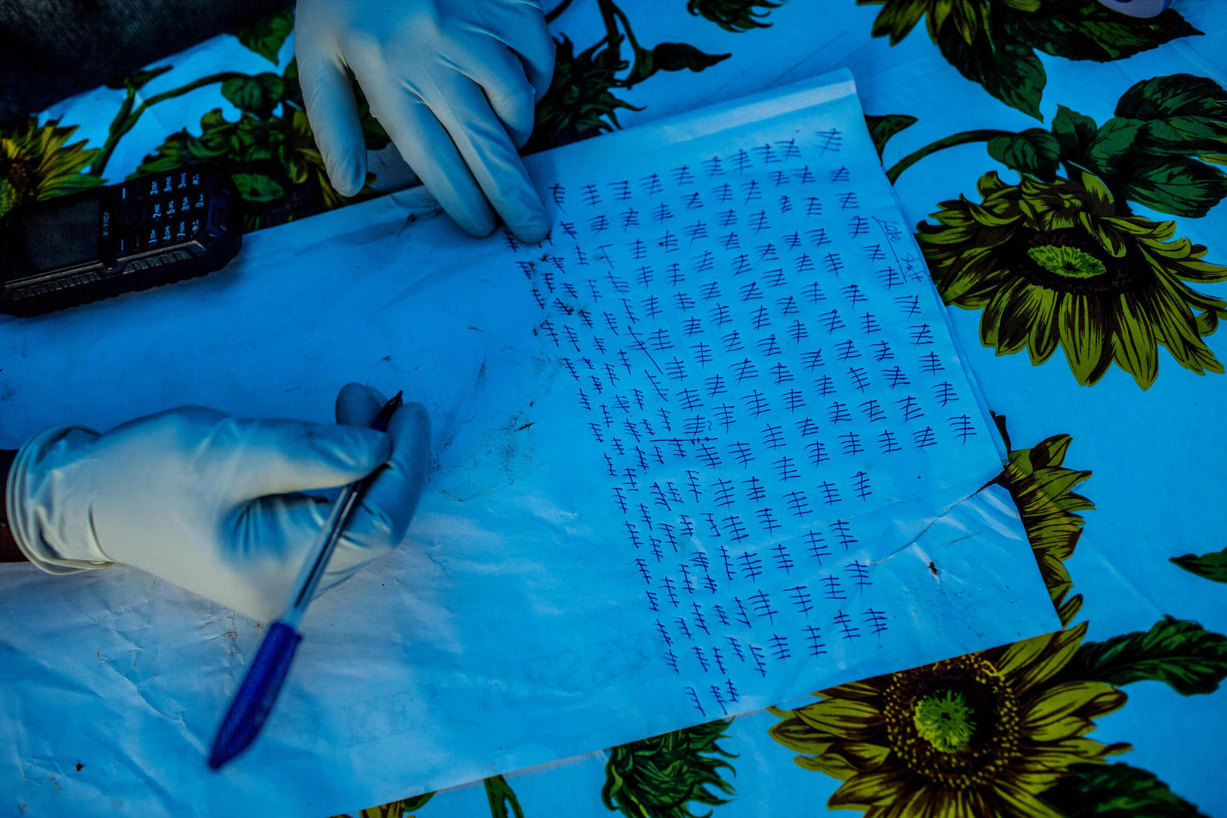 A government health worker keeps tally of those who pass an Ebola quarantine checkpoint in the road leading from Freetown to Kenema, Sierra Leone on Saturday August 16, 2014. The government of Sierra Leone has set up numerous checkpoints leading into and out of heavily Ebola affected areas. (Pete Muller/Prime for the Washington Post)