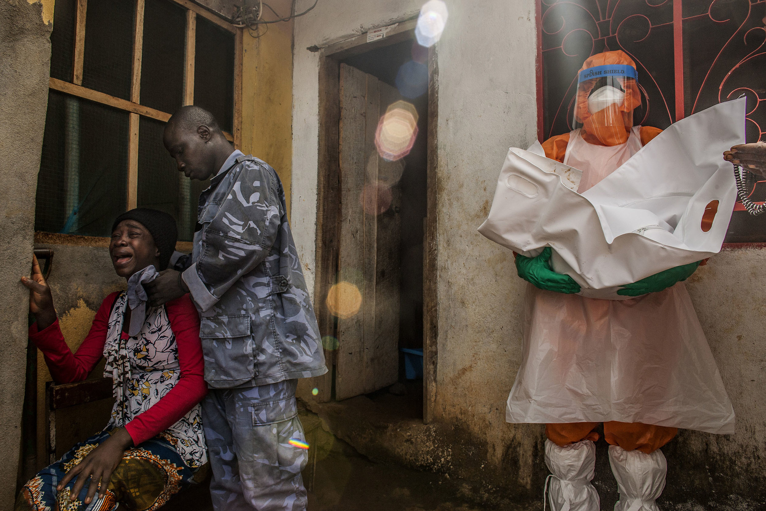 The Kabia family mourns as the body of their 1-day-old baby is removed by a member of a safe burial team outside their home in the Hill Cut neighborhood of Freetown, Sierra Leone on Wednesday, November 26, 2014. While the baby was not a confirmed Ebola case, the government of Sierra Leone mandates that all deaths in heavily Ebola-affected districts be treated as potential Ebola cases and buried in accordance with strict safety procedures. The bodies of Ebola victims are extremely infections and contact with them is a major source of disease transmission.  (Pete Muller/Prime for National Geographic)