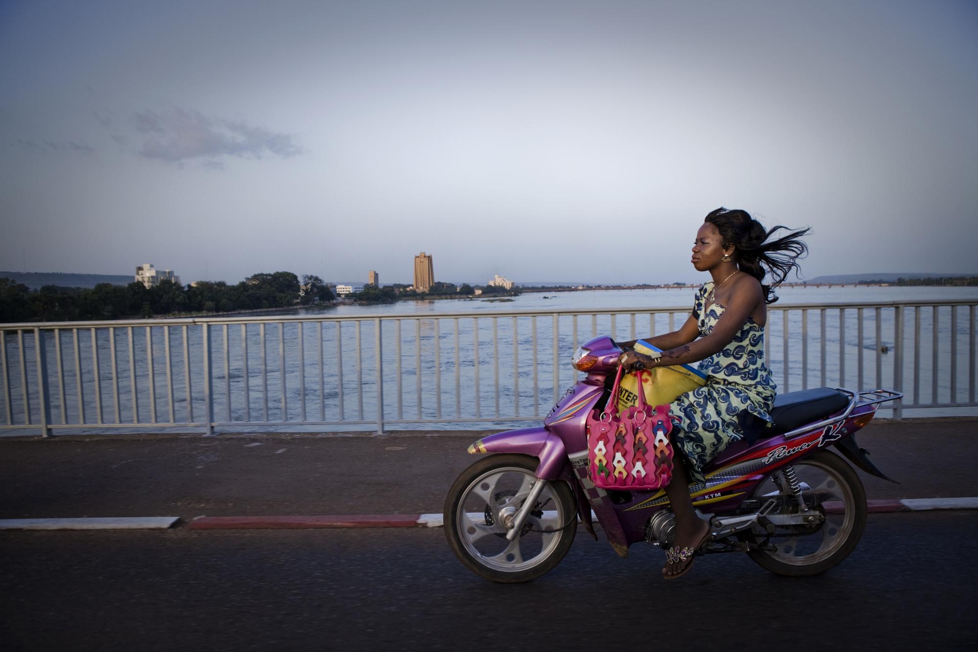 Bamako, Mali. SEPTEMBER 2013. A woman rides her motorcycle across the Niger River in Bamako, Mali. 