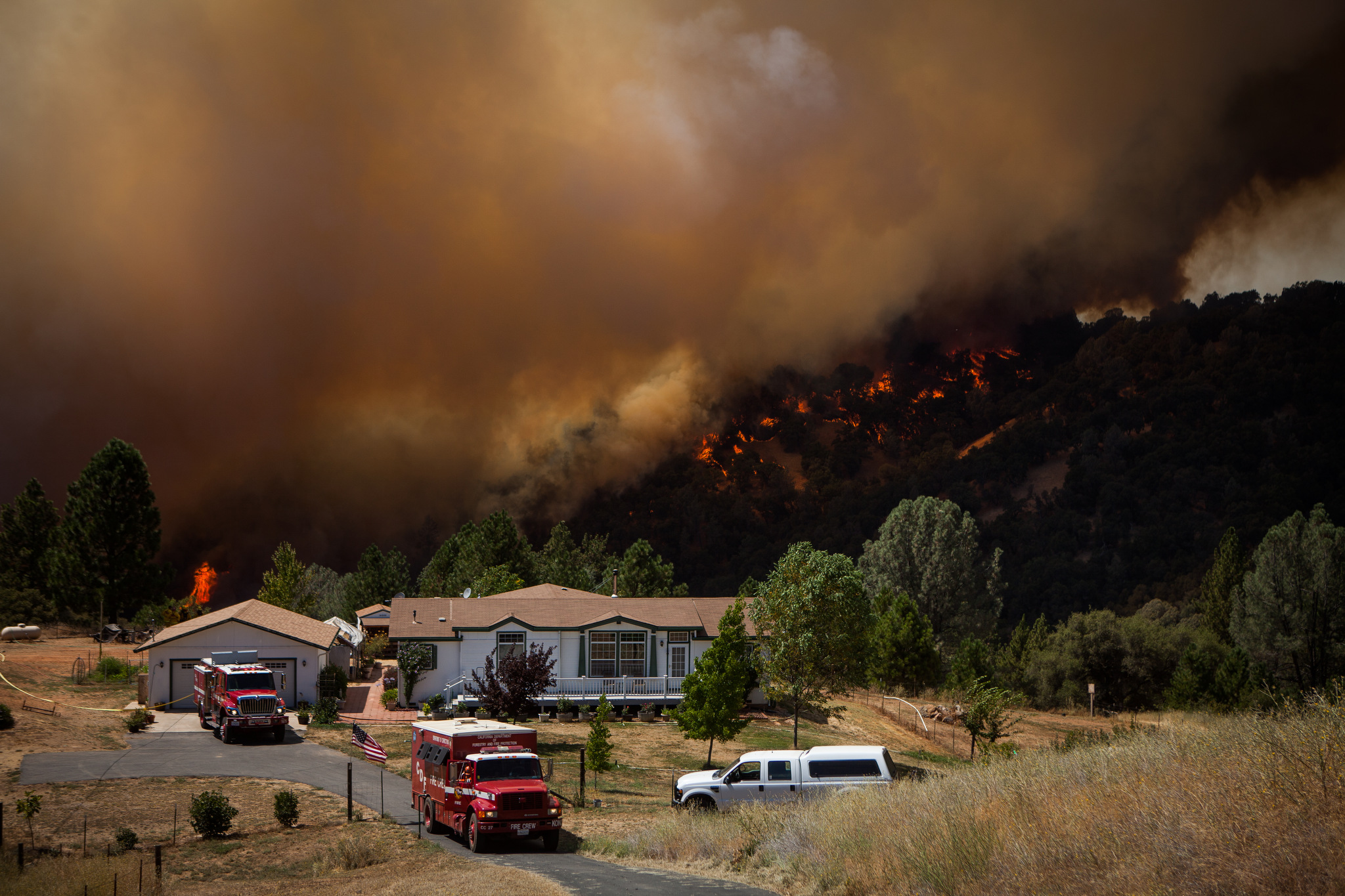 Firefighters protect an evacuated home while the Sand Fire burns behind it near Plymouth, California, July 26, 2014. The Sand Fire destroyed 20 homes and burned more than 4,200 acres near the town of Plymouth.