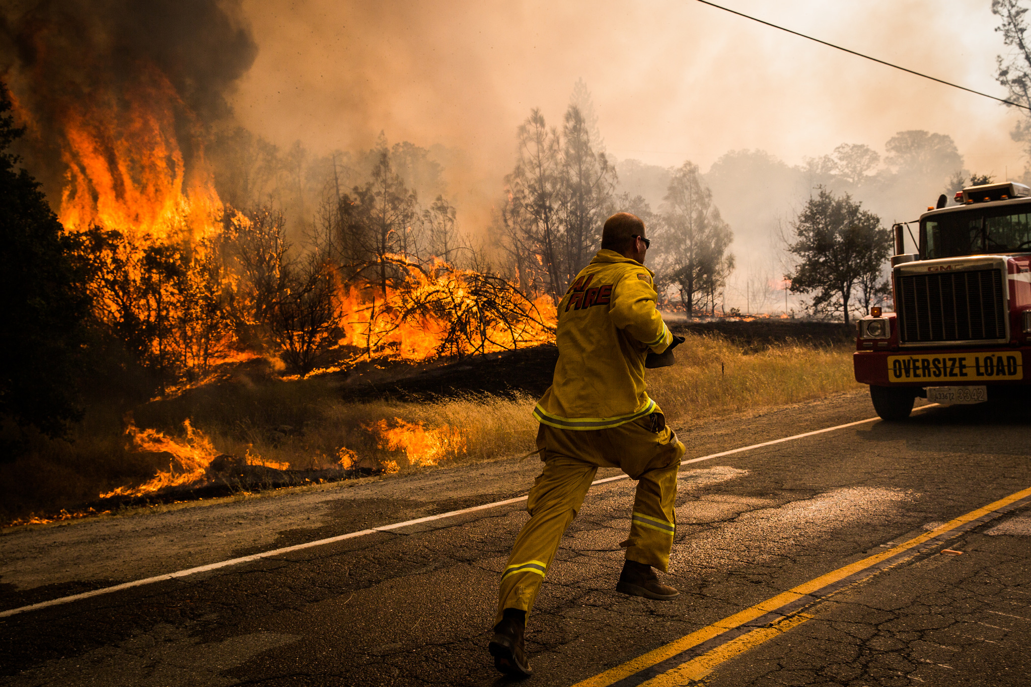 A firefighter runs to move a truck before it's overrun by a spot fire on the Rocky Fire in Lake County, California on July 30, 2015. As of August 5, the fire had consumed 69,600 acres and is one of 23 wildfires burning in California.