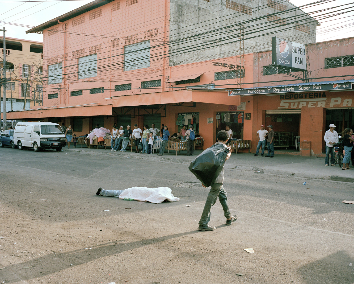 Merchants go about their business despite a body in the middle of the street in San Pedro Sula, Honduras.