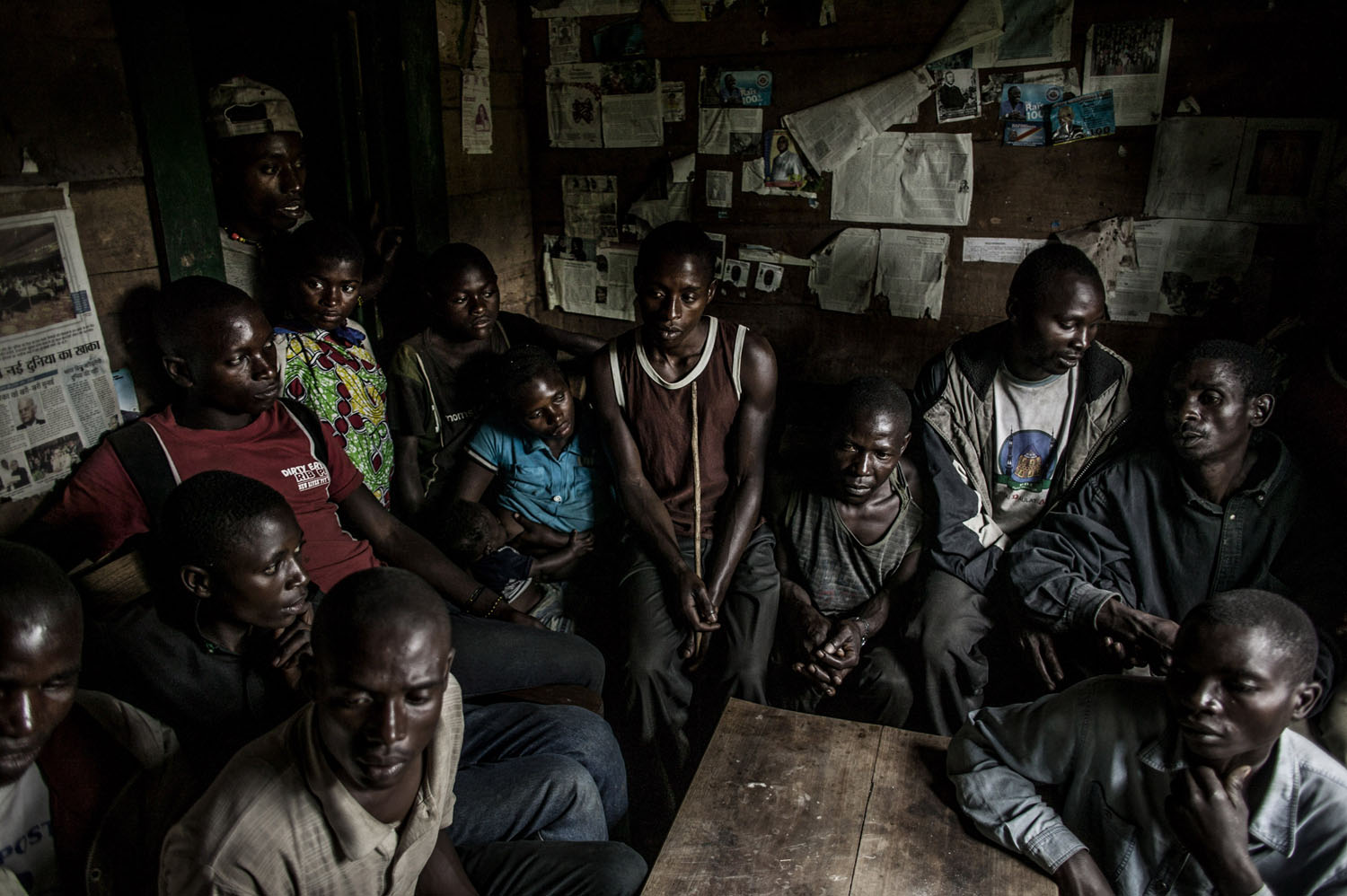 The men of the Kanyabugoyi family gather inside their family home in the village of Rugare, which was recently wrest from M-23 rebels by the Congolese army. The family fled their home in August after being continually harassed by M-23 rebels. When they returned on Monday, 28 October, they found their home had been broken into and many of their belongings by M-23 forces.