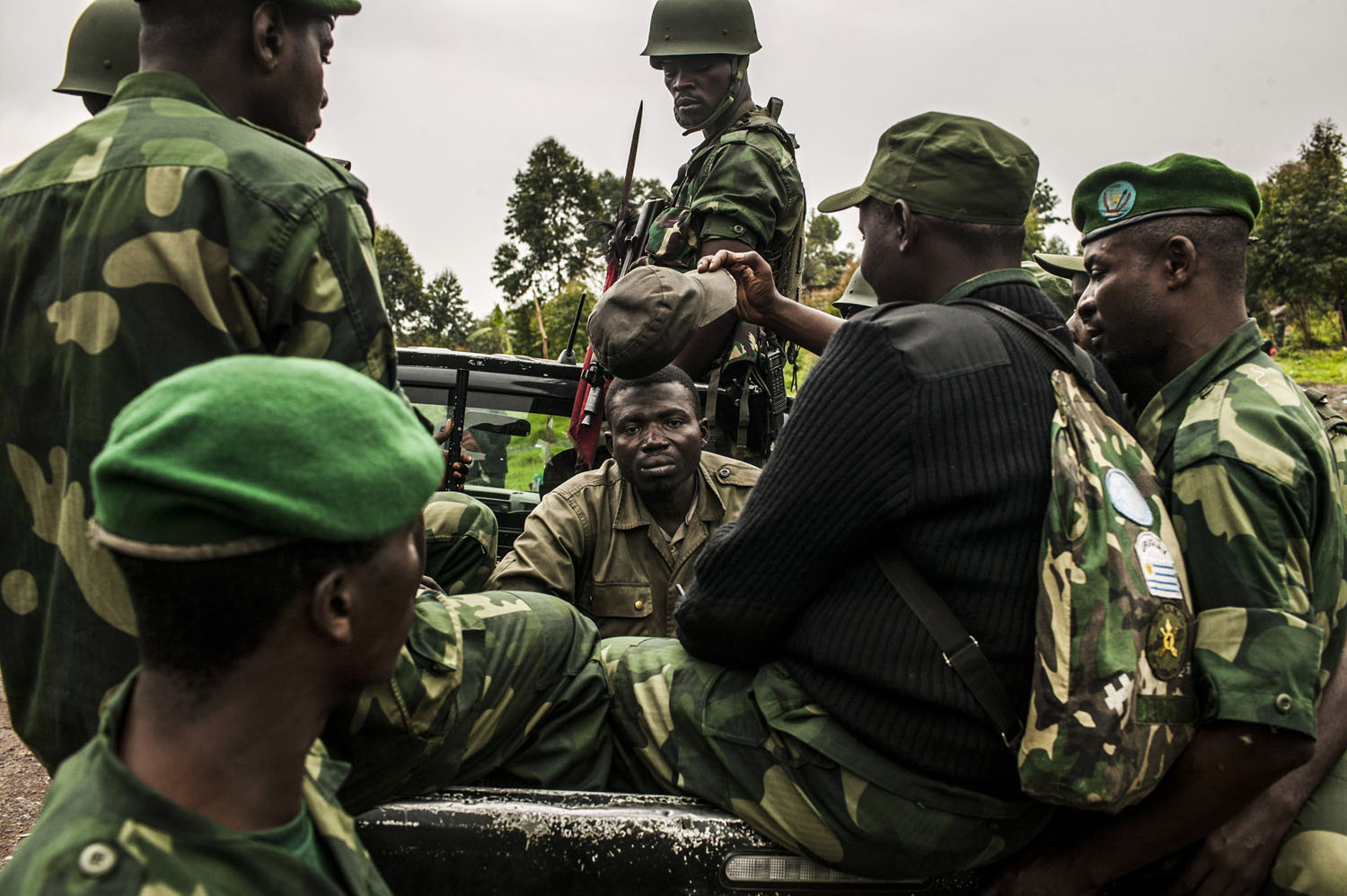 A surrendered rebel from the M-23 rebellion (center, seated) is transported by members of the FARDC from the frontline near the village of Kibati, north of Goma.
