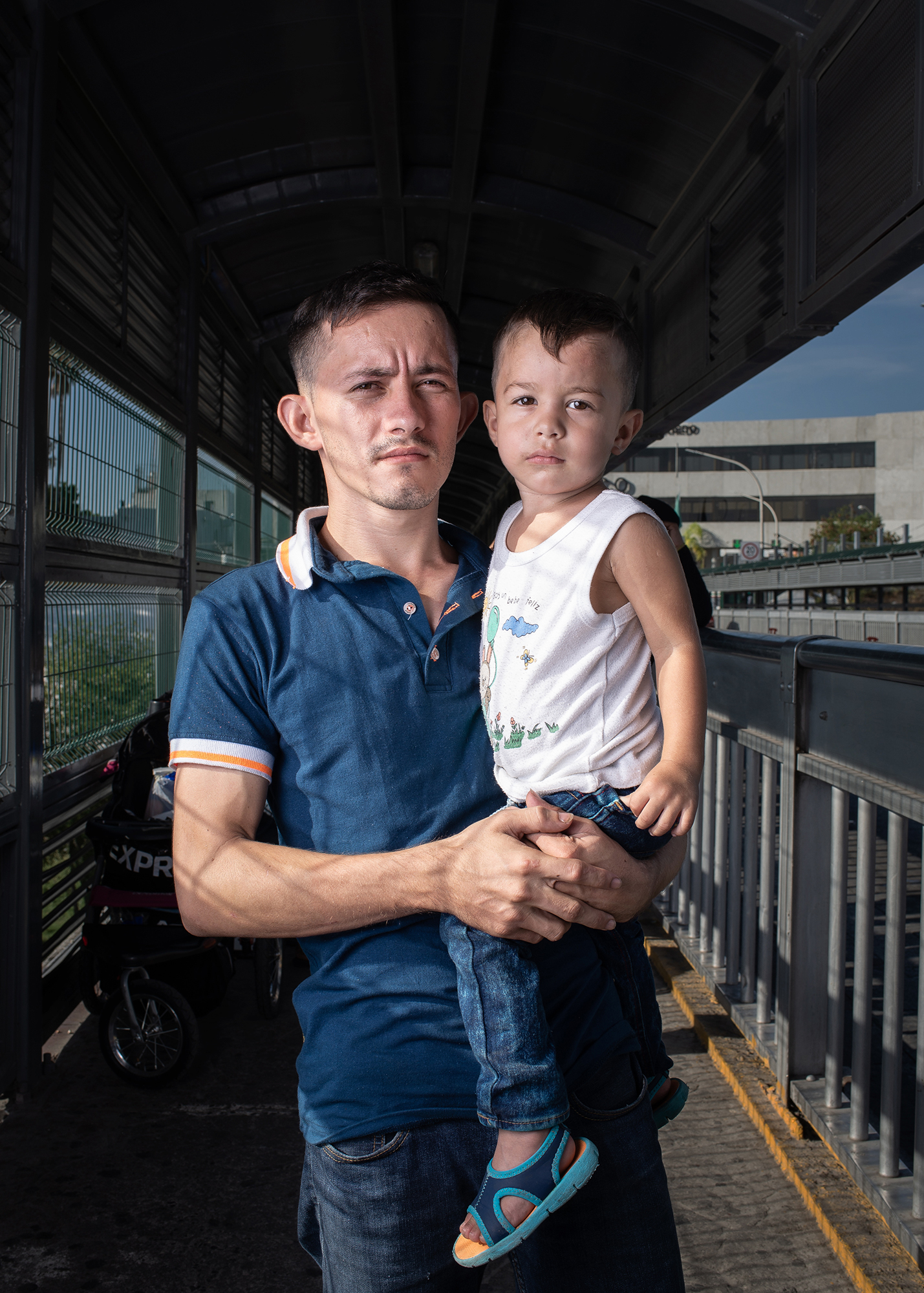 Portrait of Alfredo (26 years old) and his son Alex (1 year and 4 months), from Honduras at Laredo / Nuevo Laredo International Bridge. Alfredo decided to leave his homecountry due to the economic and social crisis it is facing. He approached the border to ask for asylum and start a new and better life. Laredo / Nuevo Laredo International Bridge. June 23rd, 2018. Photographer: Luján Agusti. (Model Release)