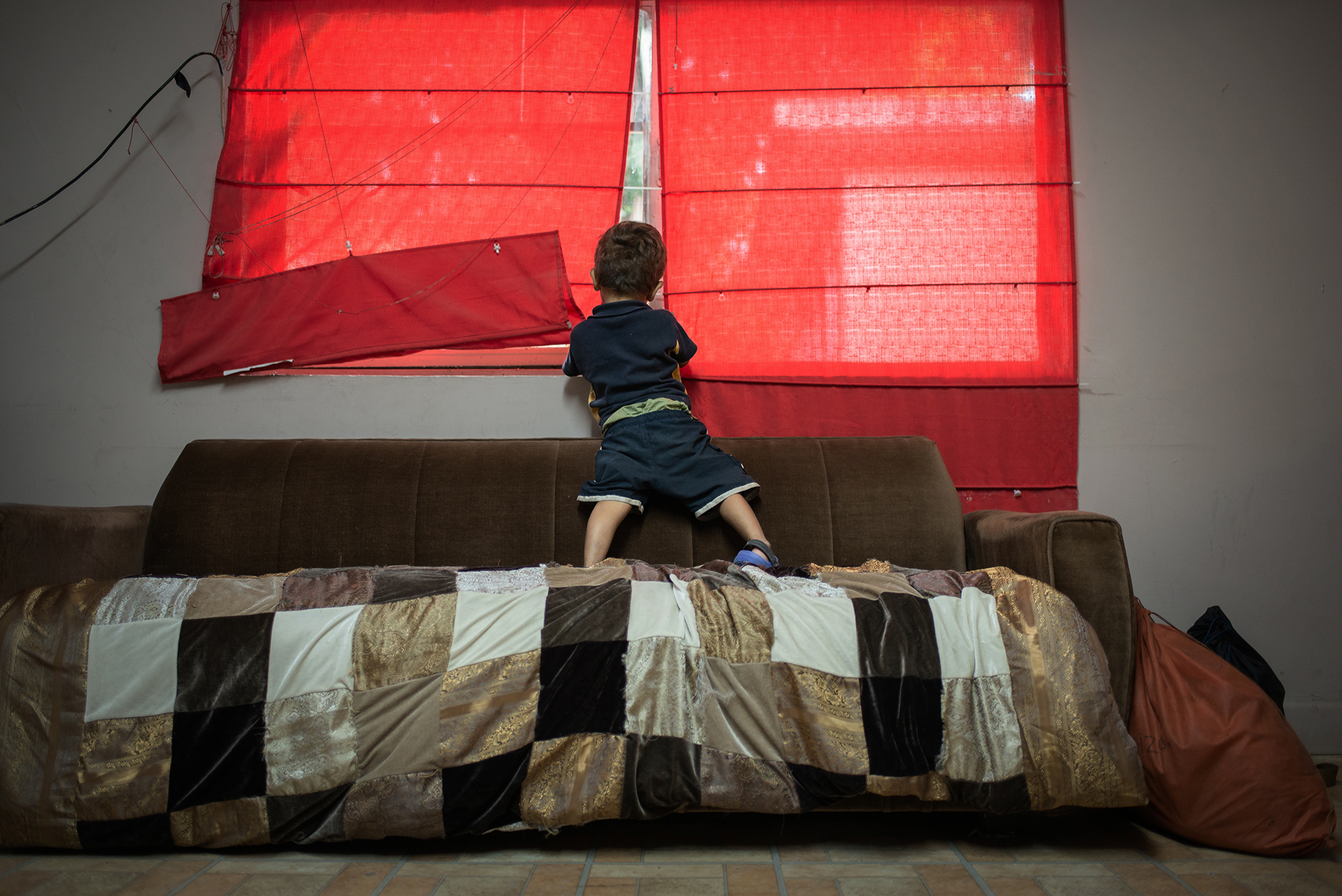 """Denis Jose (3 years old), from Honduras looks through the window at """"Casa del Migrante Frontera Digna"""" created by priest Jose Guadalupe Valdes Alvarado. Her mother Diana and him left their homecountry Honduras due to the violent situation her country is facing; """"I didn't want that future for my kid"""", she said. """"Casa del Migrante Frontera Digna"""" was created to provide lodging for migrants from different countries who arrive after long journeys that last several months to cross into the United States. Immigrants can spend three nights in the shelter where they are offered beds, food, hygiene items and a space to regain strength. Piedras Negras, Coahuila, Mexico. June 21st, 2018. Photographer: Luján Agusti."""