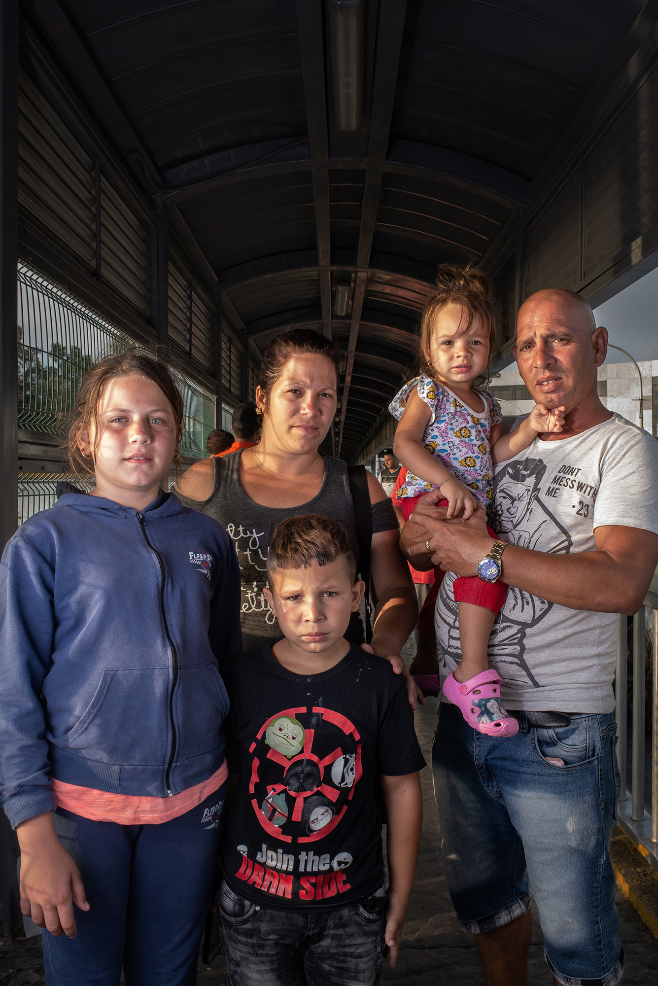 Portrait of Lorena (12), Laurel (31), Raydel (7), Yarena (2), and Raydel (45), from Cuba at Laredo / Nuevo Laredo International Bridge. They decided to leave their homecountry due to the economic and social crisis. They approached the border to ask for asylum and start a new and better life. Laredo / Nuevo Laredo International Bridge. June 25th, 2018. Photographer: Luján Agusti.