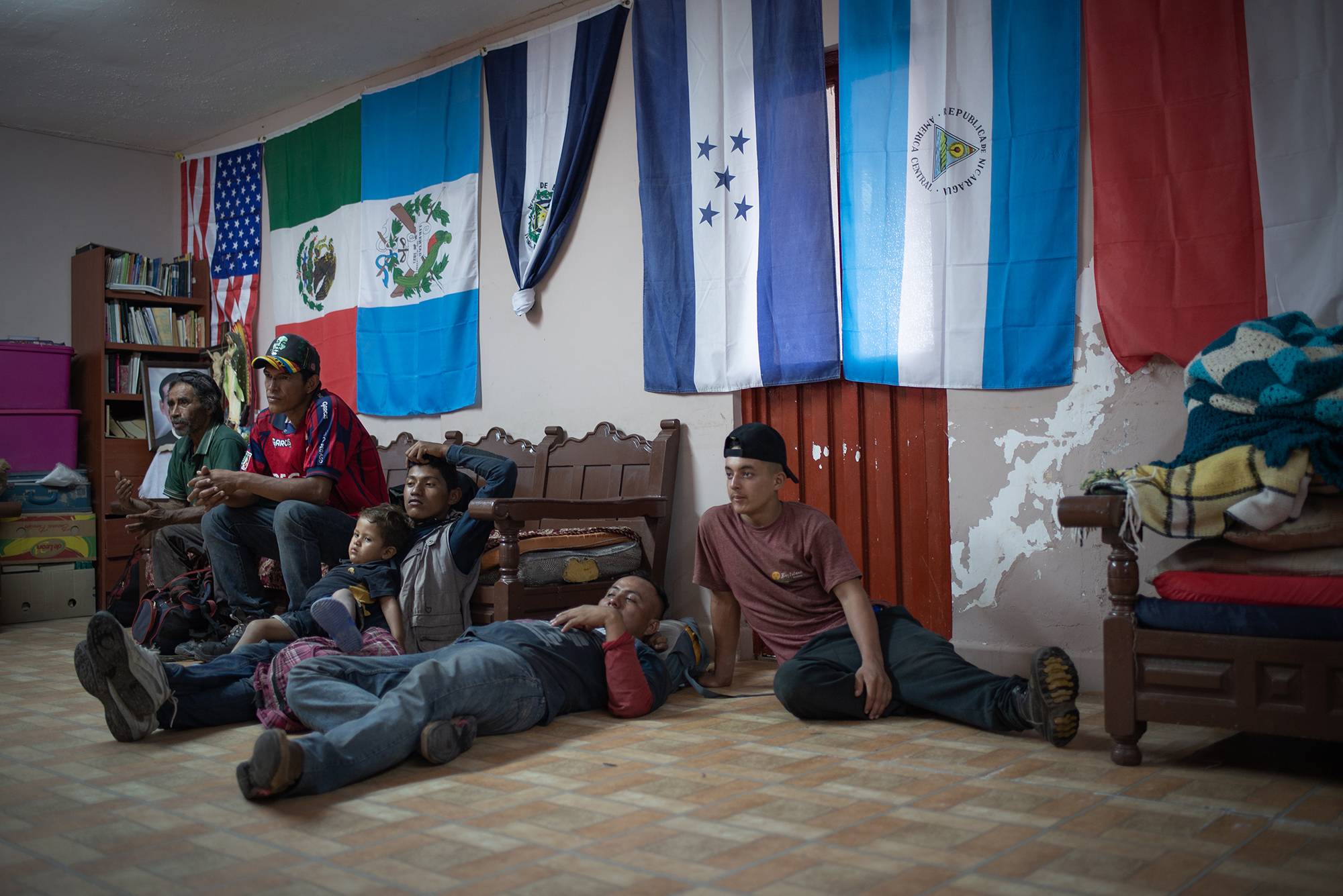 """A group of migrants hangs out and watches TV at """"Casa del Migrante Frontera Digna"""" created by priest Jose Guadalupe Valdes Alvarado. """"Casa del Migrante Frontera Digna"""" was created to provide lodging for migrants from different countries who arrive after long journeys that last several months to cross into the United States. Immigrants can spend three nights in the shelter where they are offered beds, food, hygiene items and a space to regain strength. Piedras Negras, Coahuila, Mexico. June 21st, 2018. Photographer: Luján Agusti."""