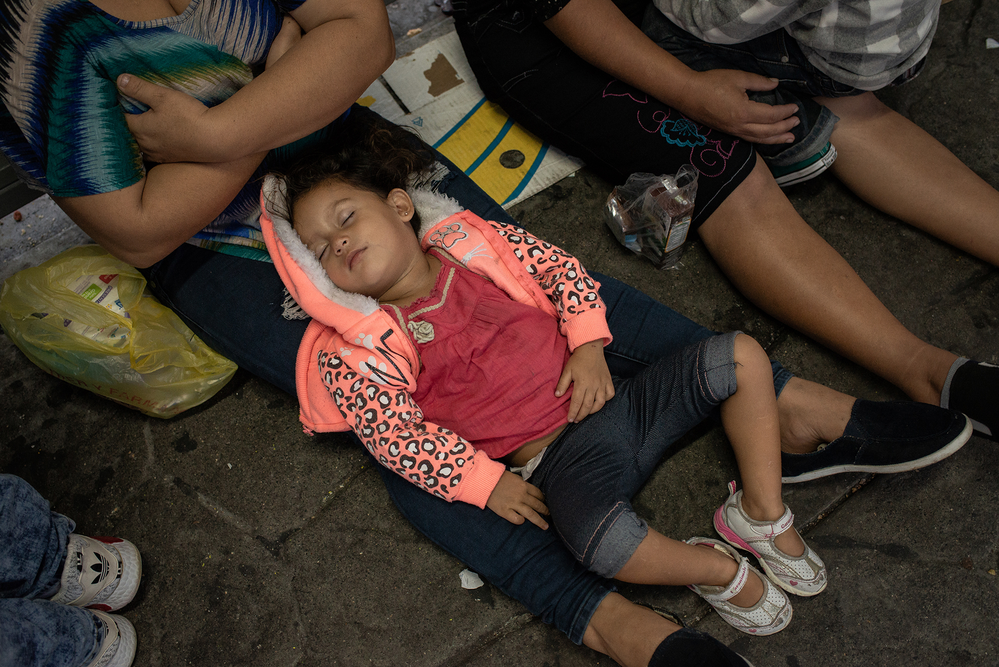 A baby sleeps in the row of the Laredo / Nuevo Laredo International Bridge. Every day a large number of people from different countries come to the border to ask for asylum. They usually spend one or two nights waiting for their turn to be taken care of. Most of them trust that the US government will help them. Laredo / Nuevo Laredo International Bridge. June 25th, 2018. Photographer: Luján Agusti.