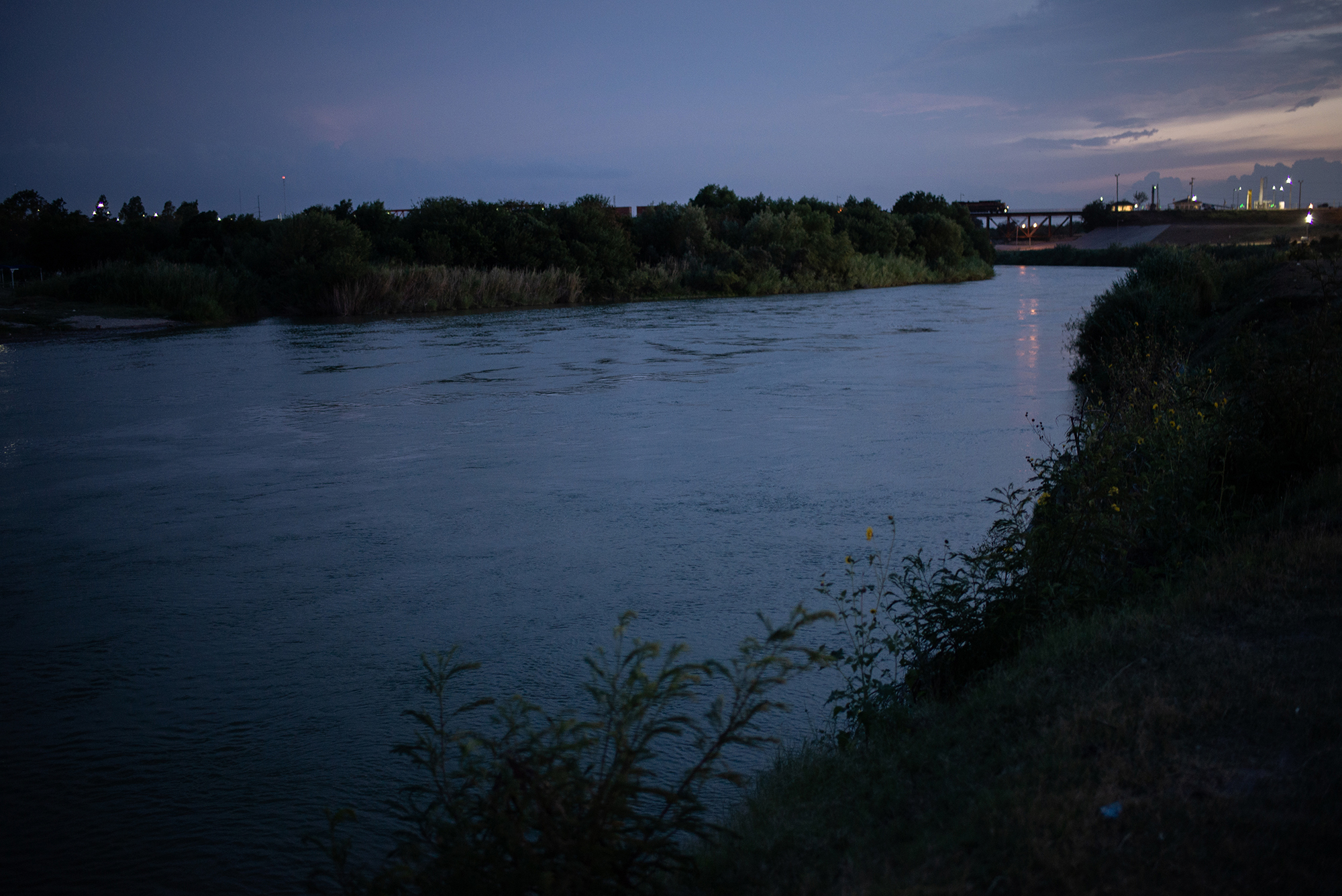Night view of the Rio Grande that separates the United States from Mexico. This river is well known for being a natural border, and to which many people submerge to reach the United States, escaping the violence and bad economic situation in their countries. Laredo, Texas, US. June 25th, 2018. Photographer: Luján Agusti.