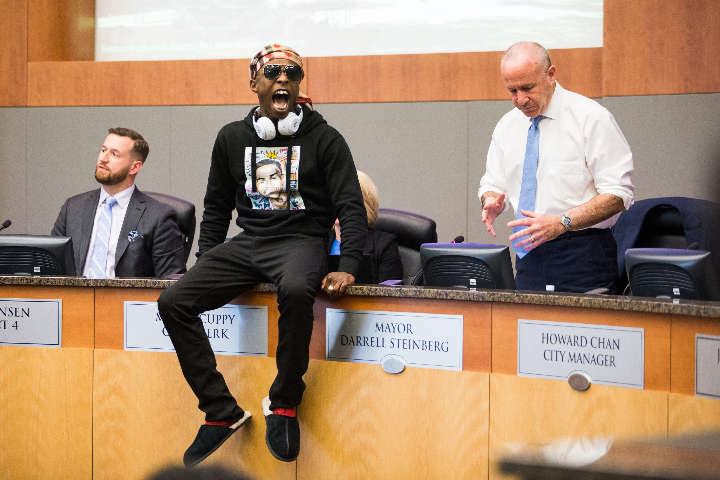 Stephon Clark's brother, Stevante Clark, angrily jumps onto the desk of Sacramento Mayor Darrell Steinberg during a city council meeting calling for public comment on the police shooting of Clark. Stevante and hundreds of protestors briefly took over both the meeting and City Hall itself.