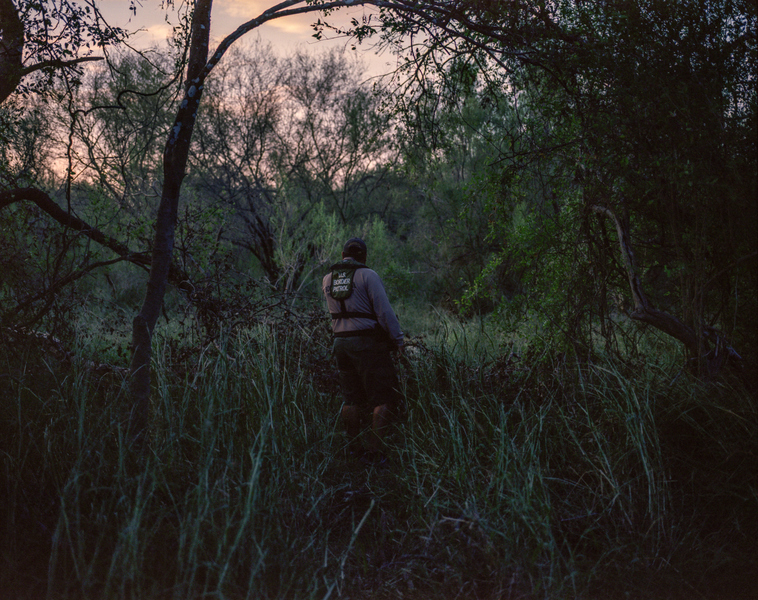 A Border Patrol agent listens for the sounds of people moving through the brush in South Texas.