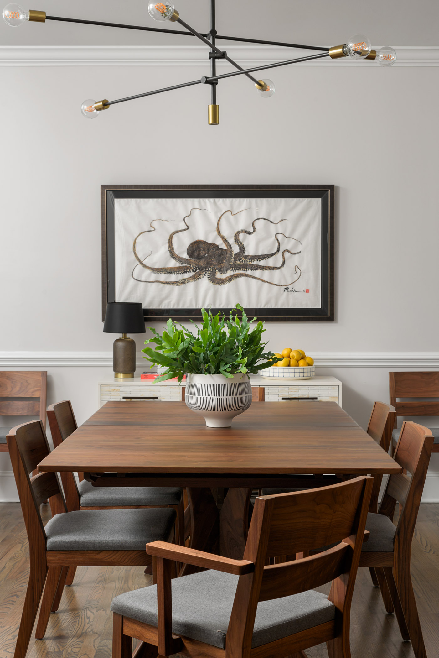 A sculptural mid-century inspired chandelier floats above a walnut dining table and chairs.