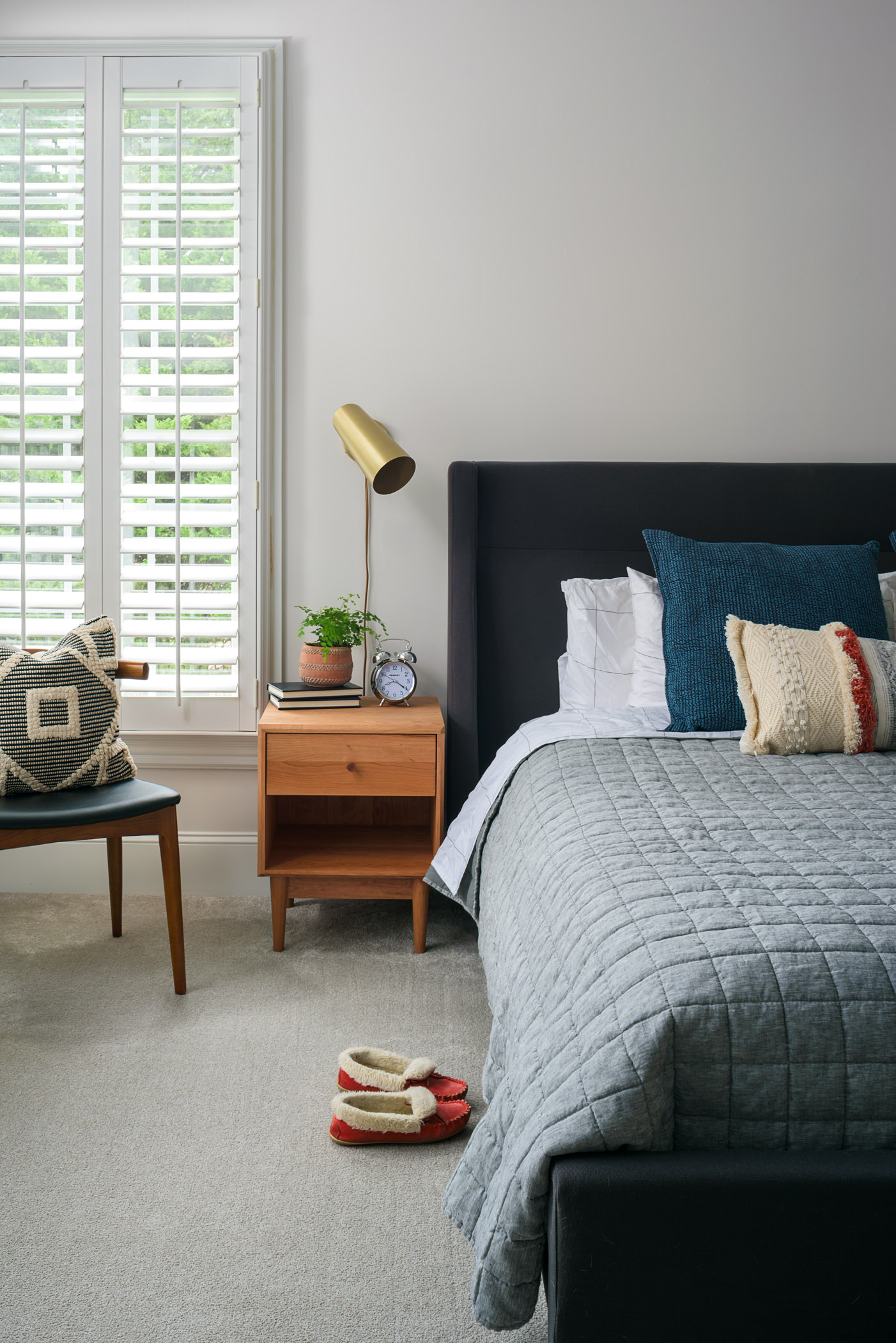A bright and airy master bedroom. Gray walls bounce lots of light around while natural woods, soft textiles, and a pop of brass warm up the room.