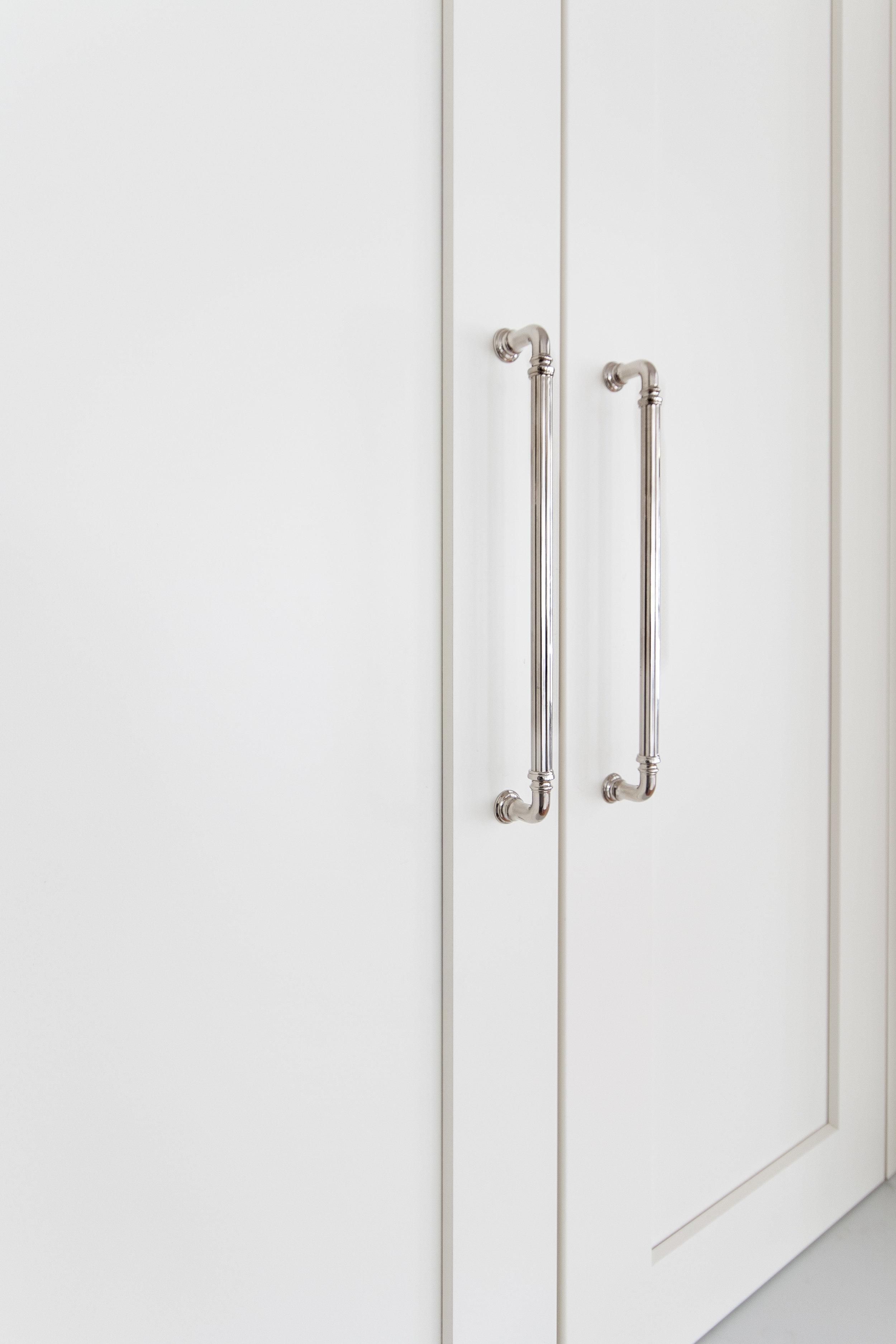 Elegant fluting on the polished nickel cabinet hardware.