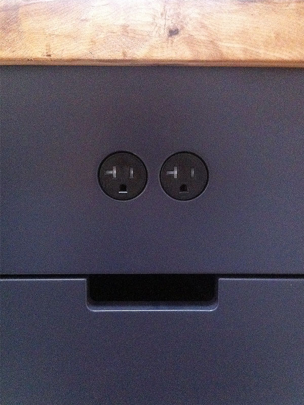 Electrical receptacles that sit flush with the surrounding surface, without visible cover plates.