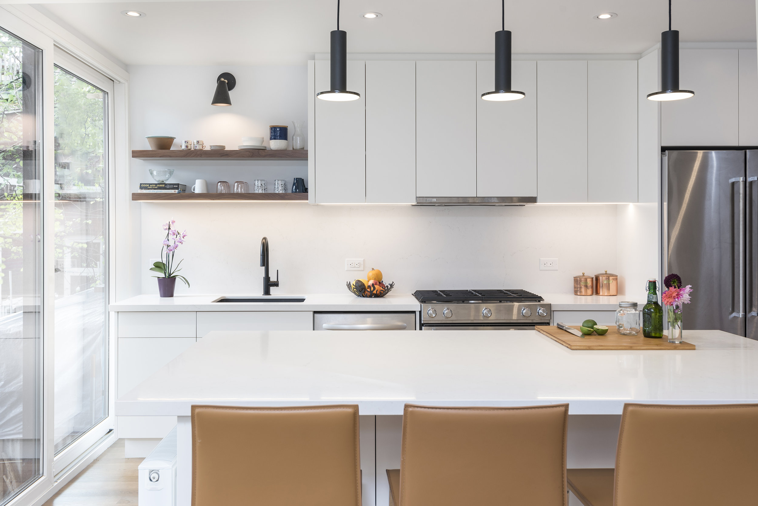 Relocated kitchen with direct access to exterior deck has a simple and elegant aesthetic.