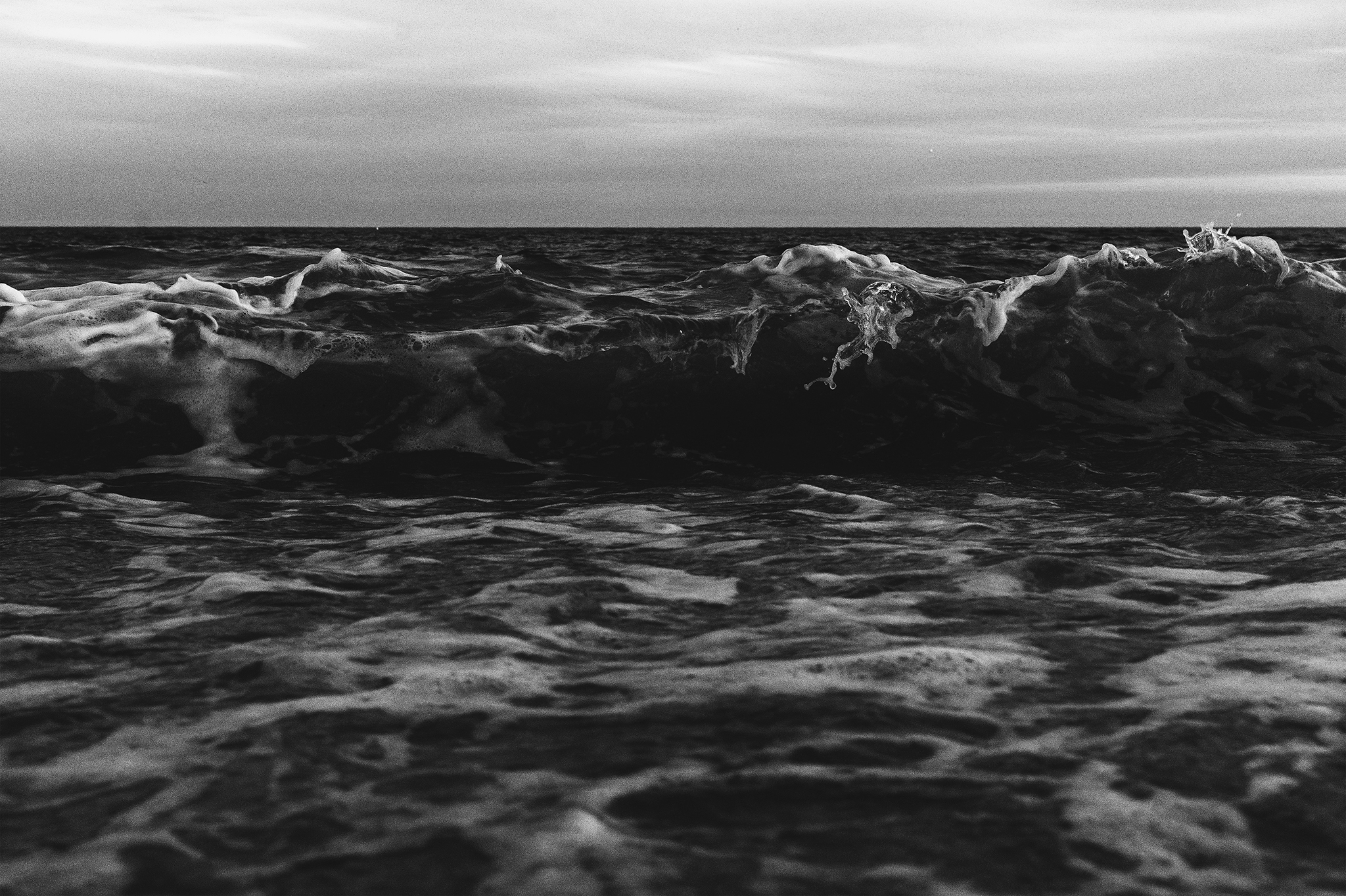 A high-contrast black and white photograph of waves as they come crashing into the sea.